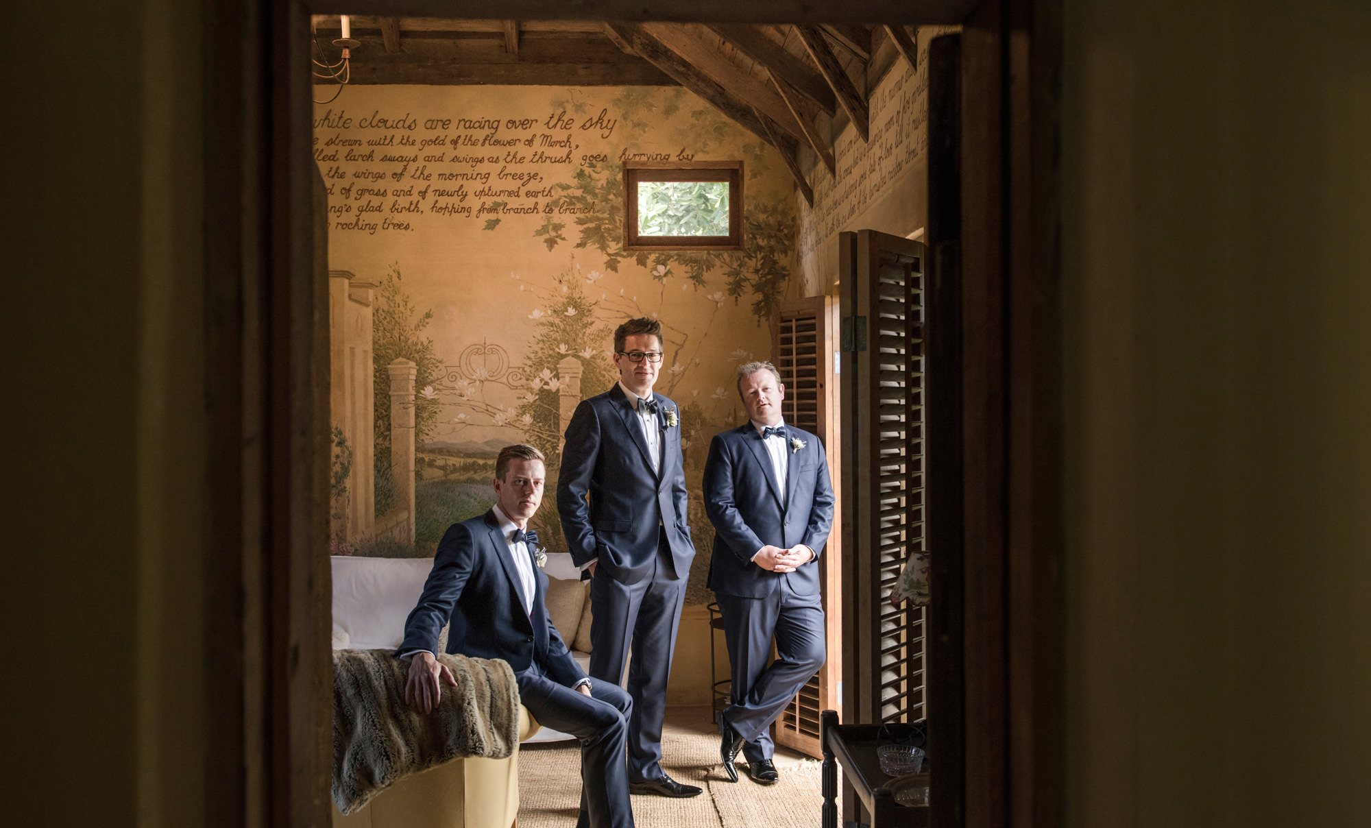 Classic portrait of groom and groomsmen in painted room wearing blue-grey suits  -  Studio Impressions Photography