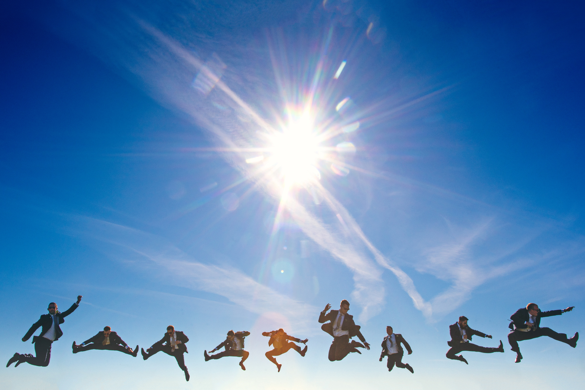 Groom and groomsmen jumping into the sky - photo by Cooked Photography