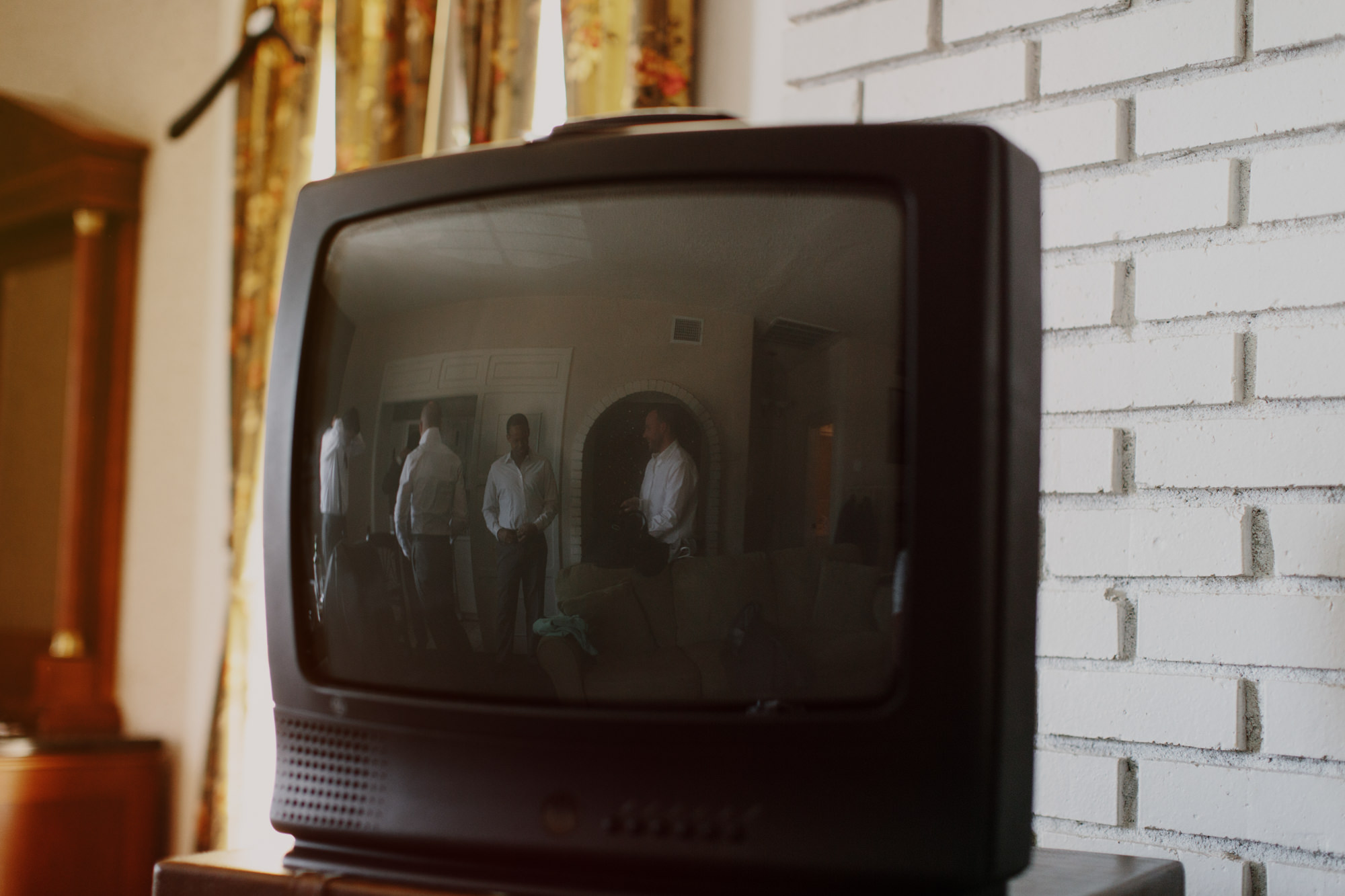 Reflection of guys getting ready in old analog TV by James Moes