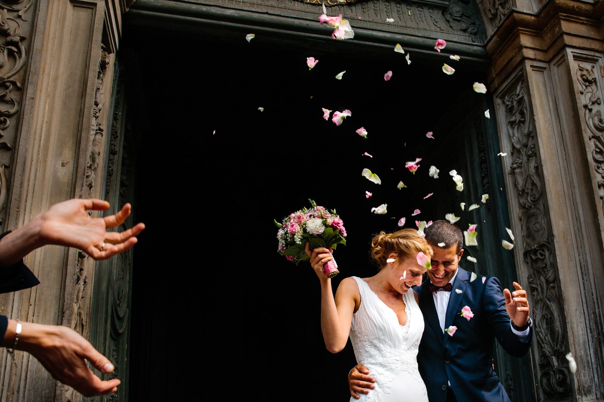 Guests throw rose petals at just married couple exiting church doors, photo by Yves Schepers, Belgium wedding photographer
