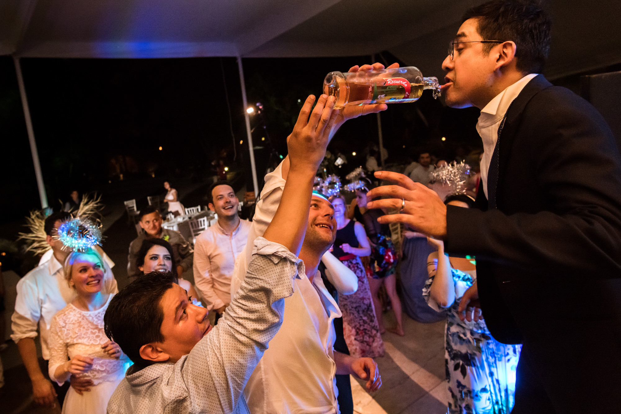 Guests pour vodka into grooms mouth photo by Fotobelle: Isabelle Hattink