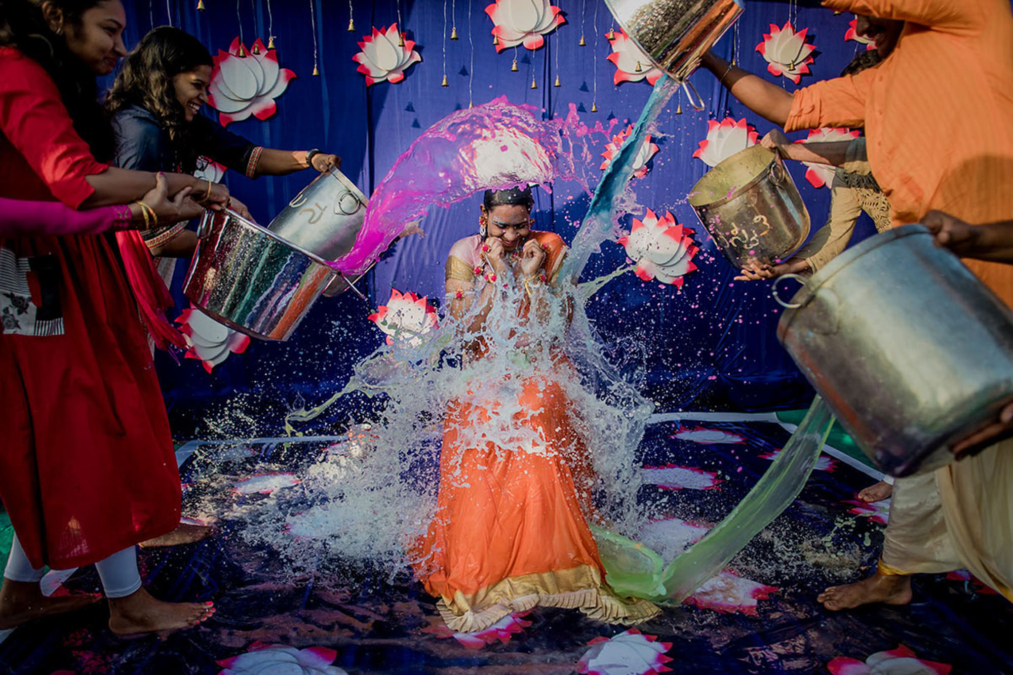 Guests throw water on happy bride - photo by Rimi Sen Photography
