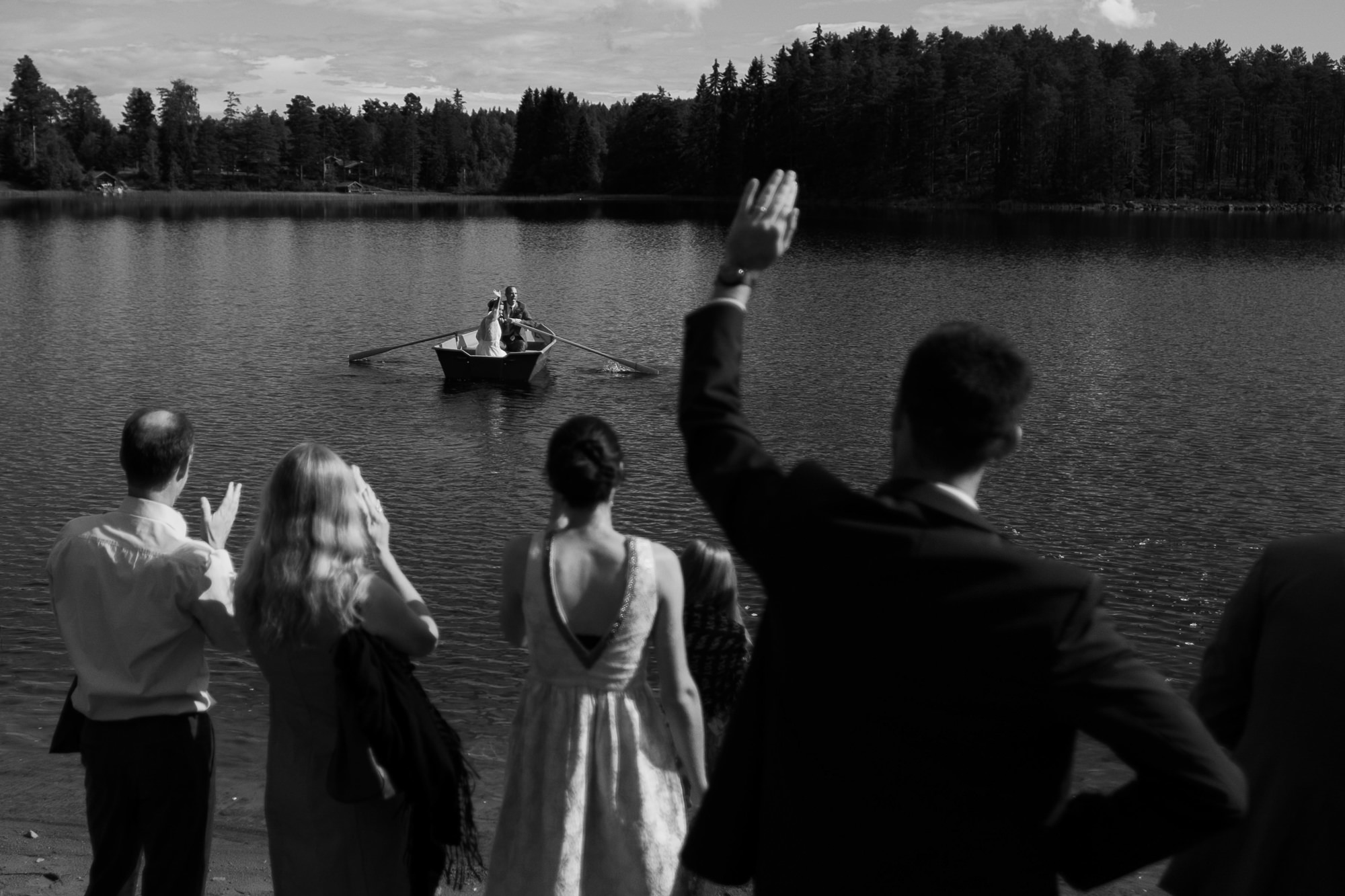 Guests wave goodbye to couple in canoe photo by Nordica Photography