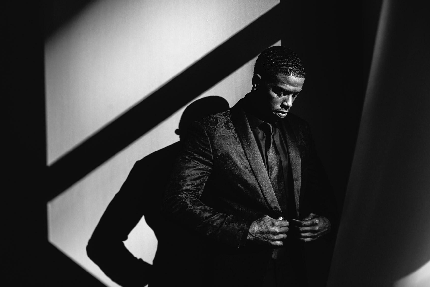Groom in black suit in dramatic window lighting by Callaway Gable