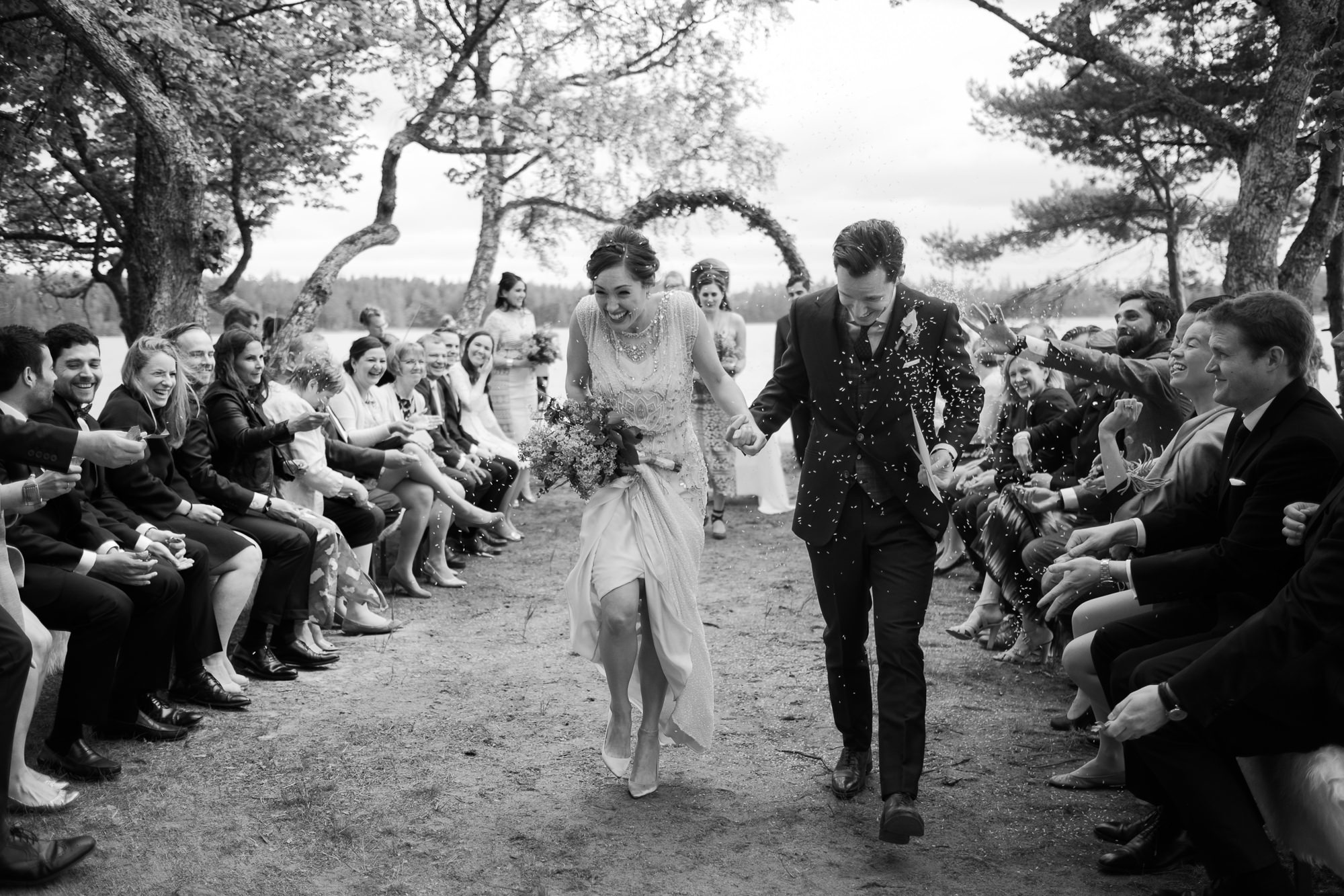 Happy couple leaves ceremony while guests throw rice photo by Nordica Photography