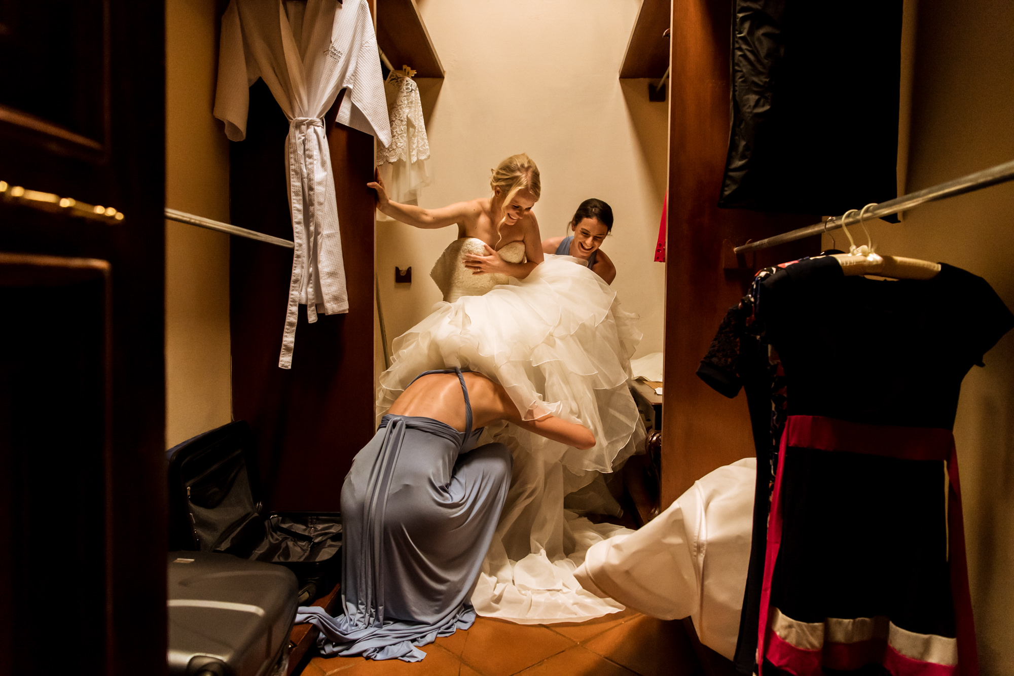 Bridesmaid underneath brides ruffled gown in closet photo by Fotobelle: Isabelle Hattink