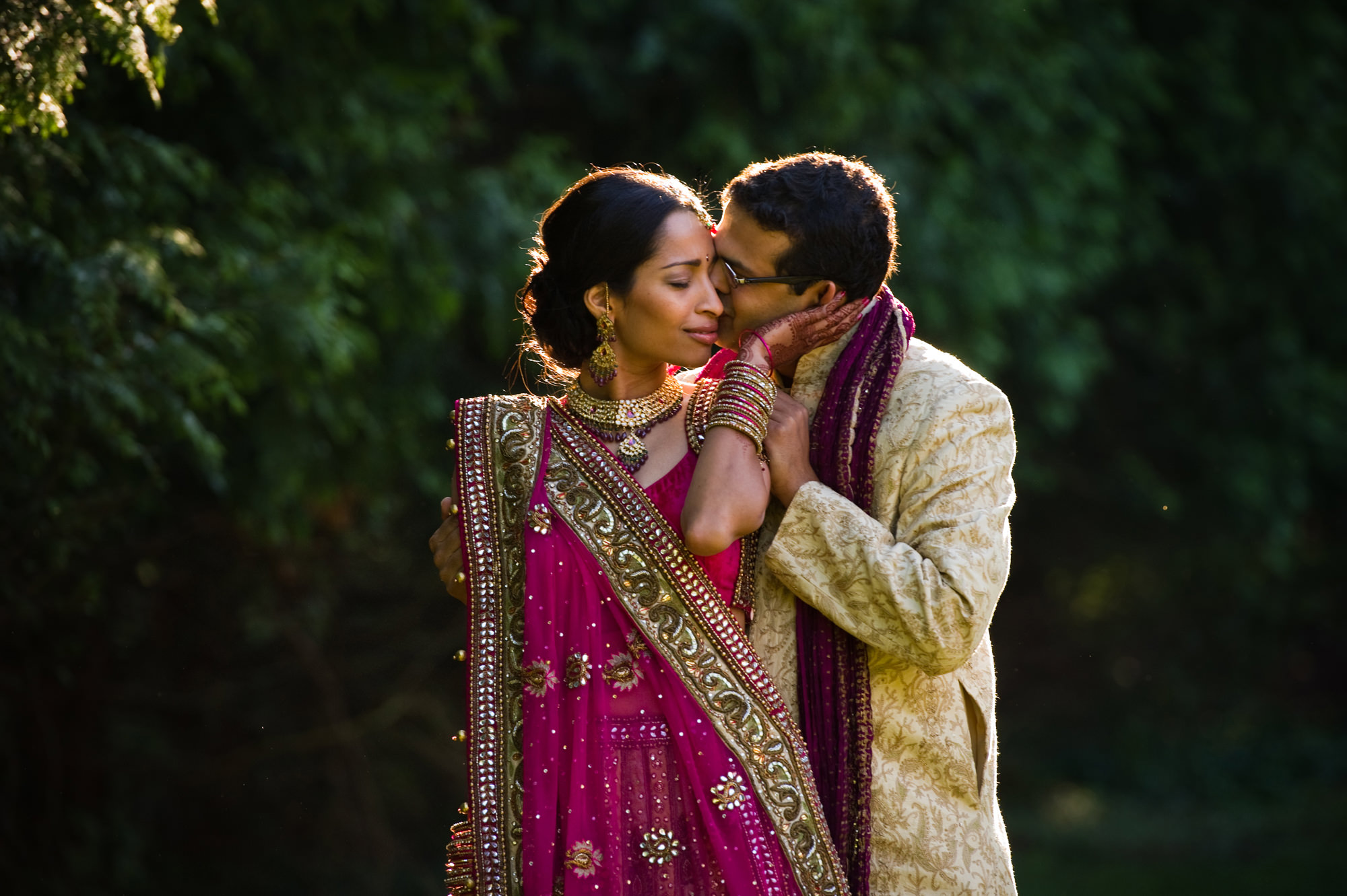 Indian bride and groom embrace in garden, by Cliff Mautner