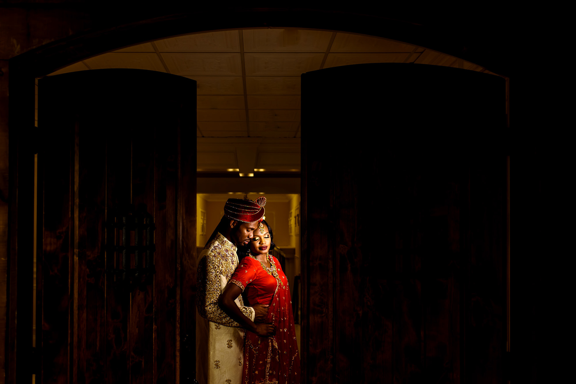 Indian bride and groom in wooden doorway - photo by Alakija Studios