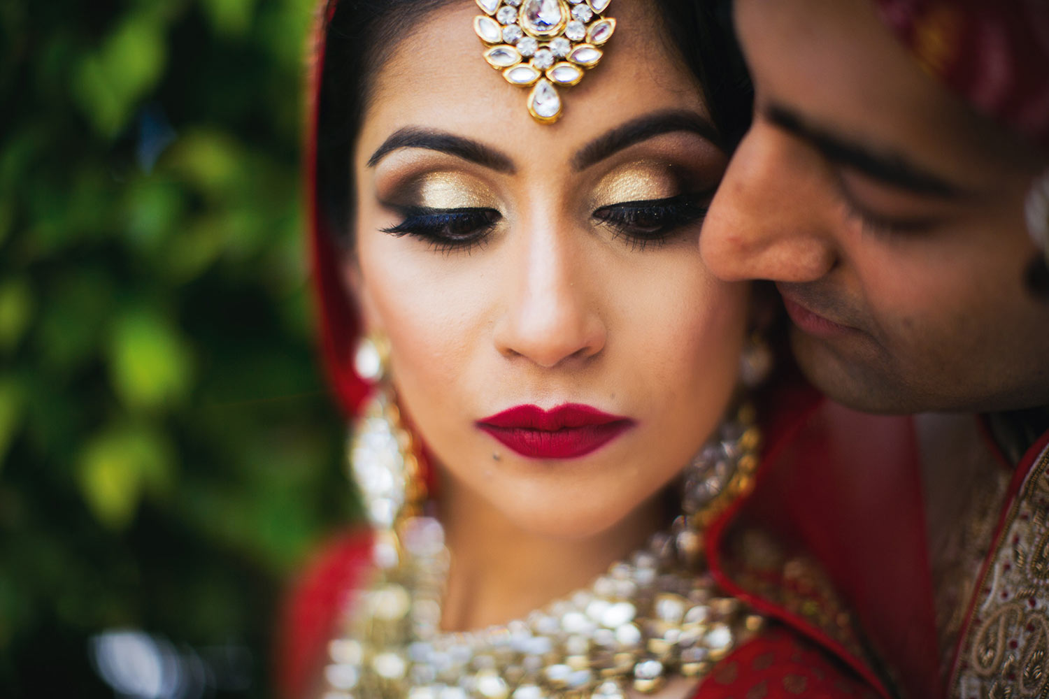 Indian bride with gold eyeshadow and red lips, with groom, by Calloway Gable