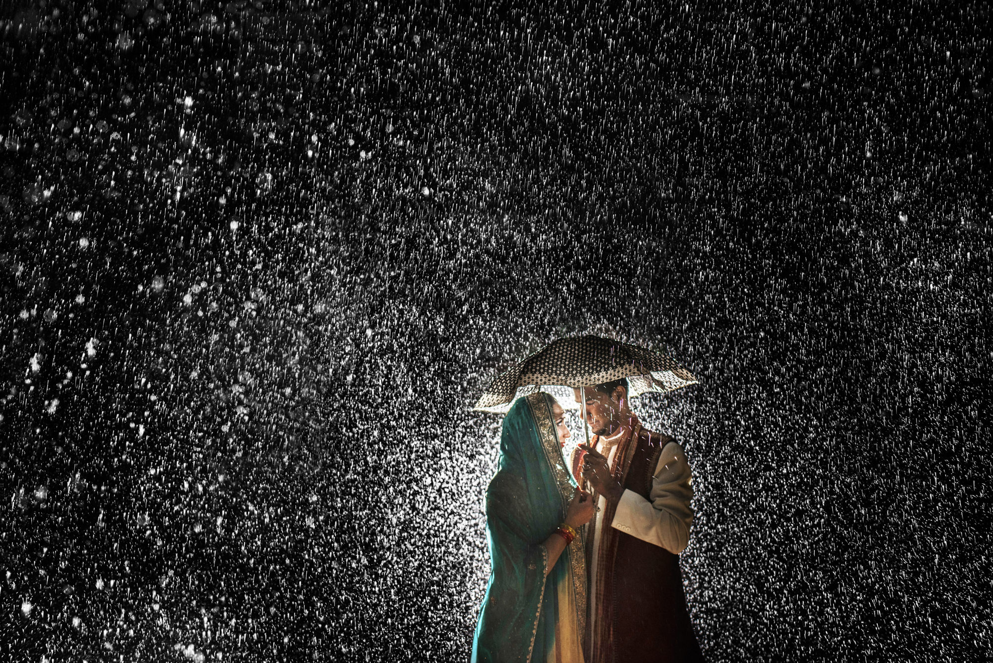 Indian couple in pouring rain under umbrella - photo by Look Fotographica