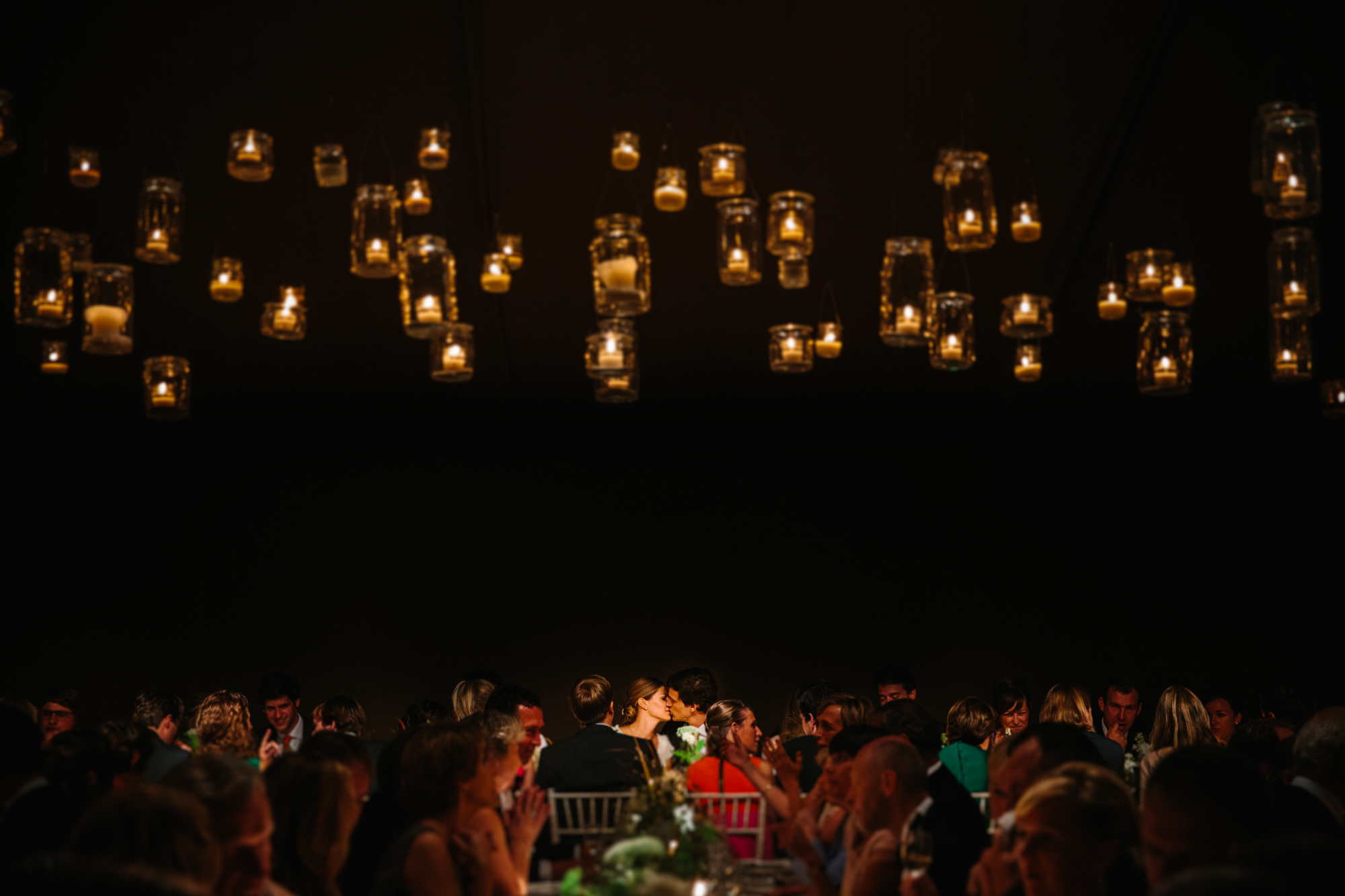 Just married couple kisses in busy candlelight reception venue  Yves Scheper Belgium wedding photographer
