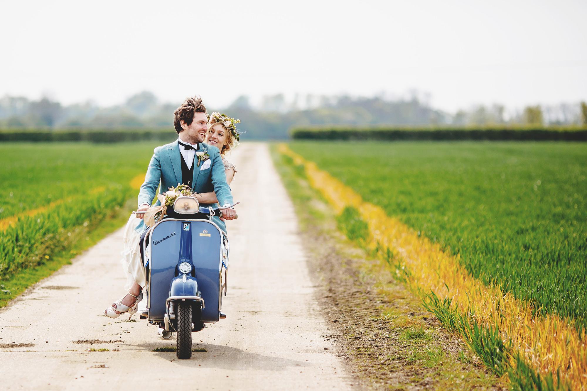 Couple leaving ceremony on blue Vespa by Ross Harvey