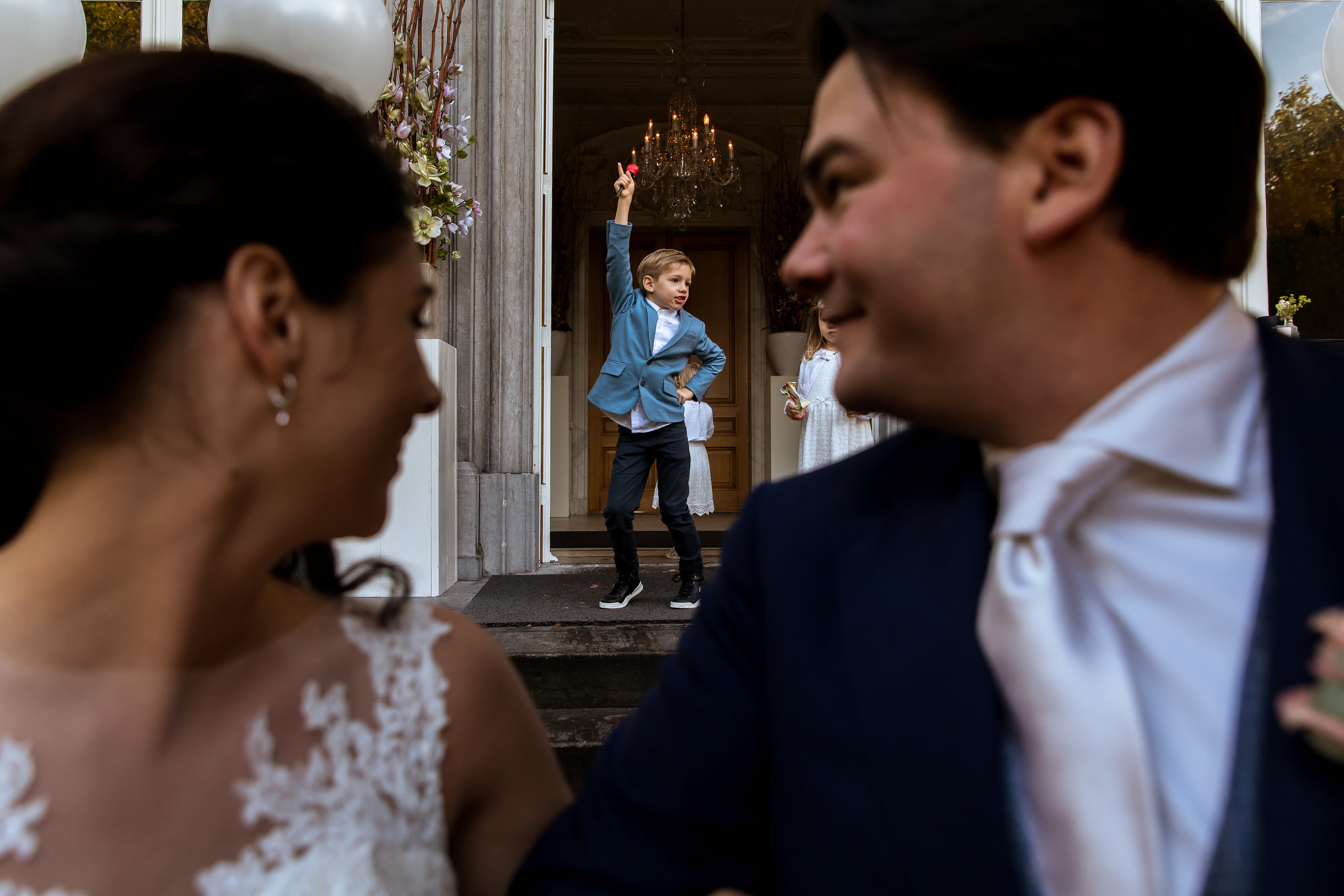 Kid dancing framed by bride and groom photo by Fotobelle: Isabelle Hattink