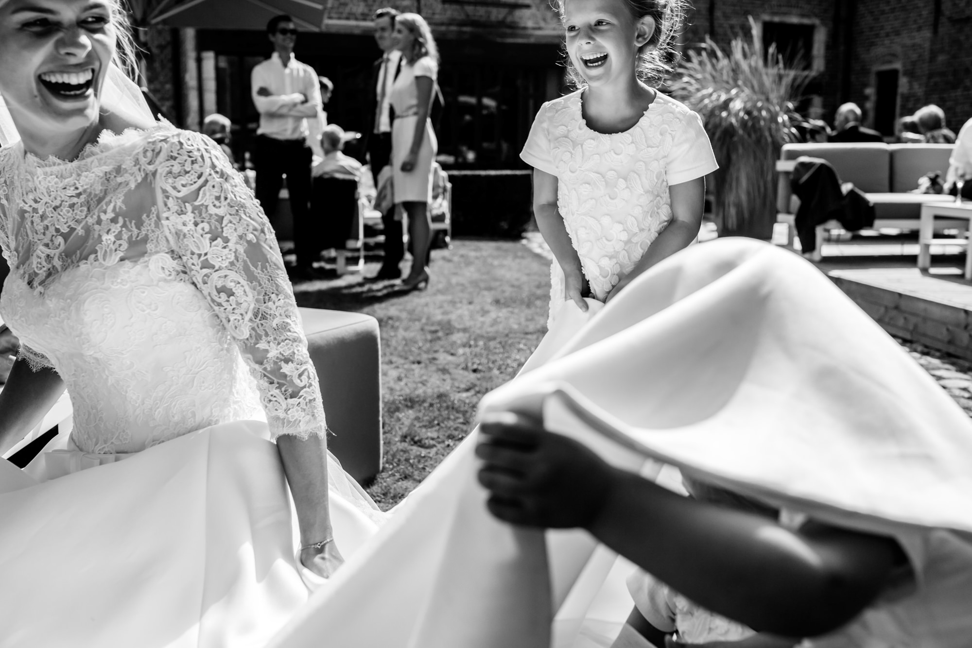 kids playing under laughing brides dress - photo by Phillipe Swiggers