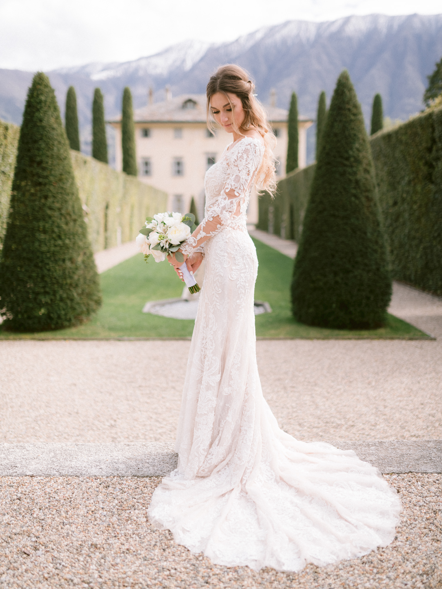 Bride in long sleeve gown with train in front of villa - photo by Gianluca Adovasio Photography