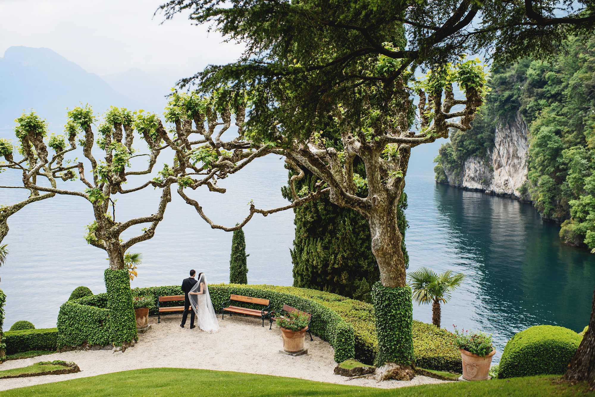 couple standing at edge of Lake Como - photo by Ross Harvey