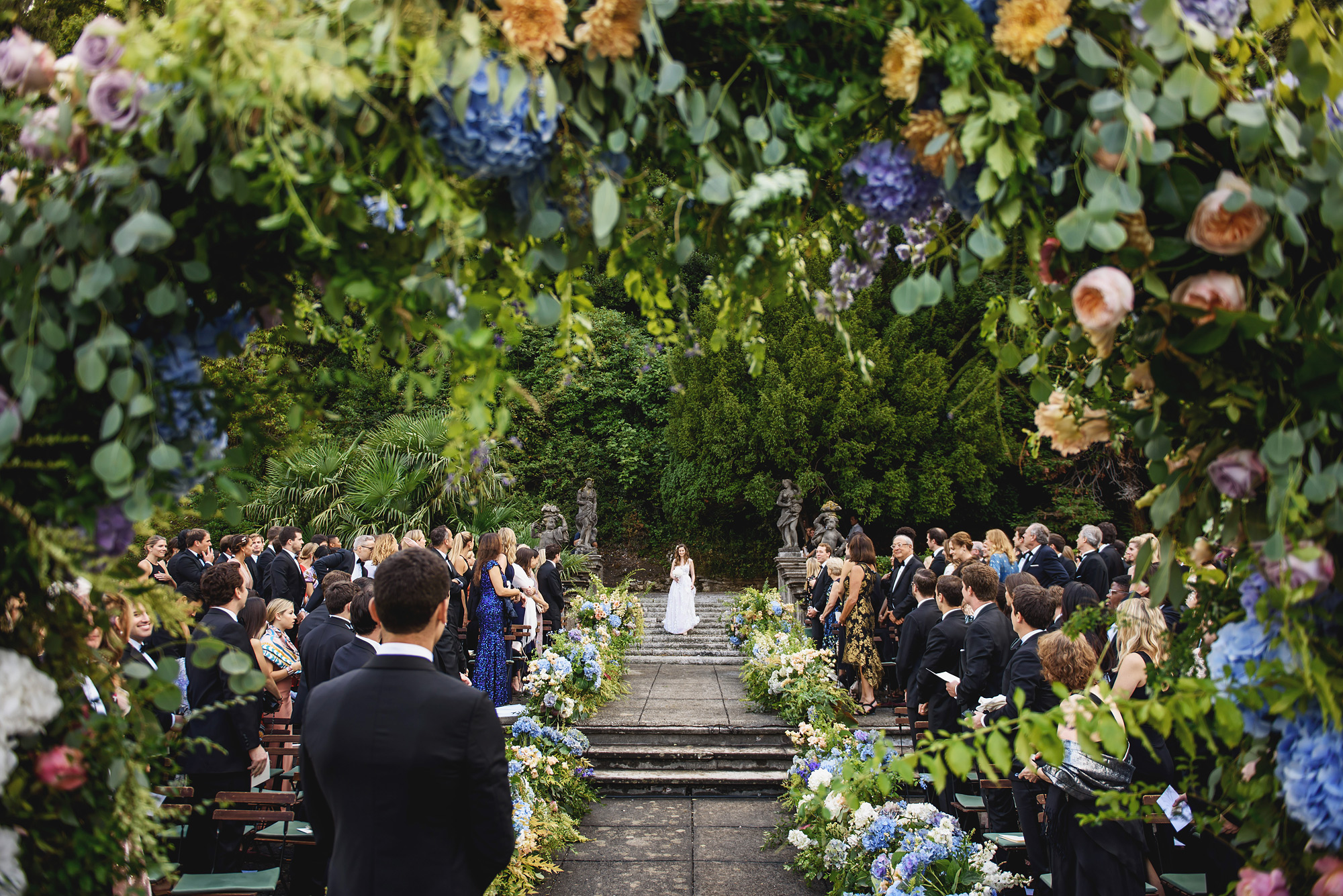 Bride comes down elaborate floral lined aisle - photo by Ross Harvey