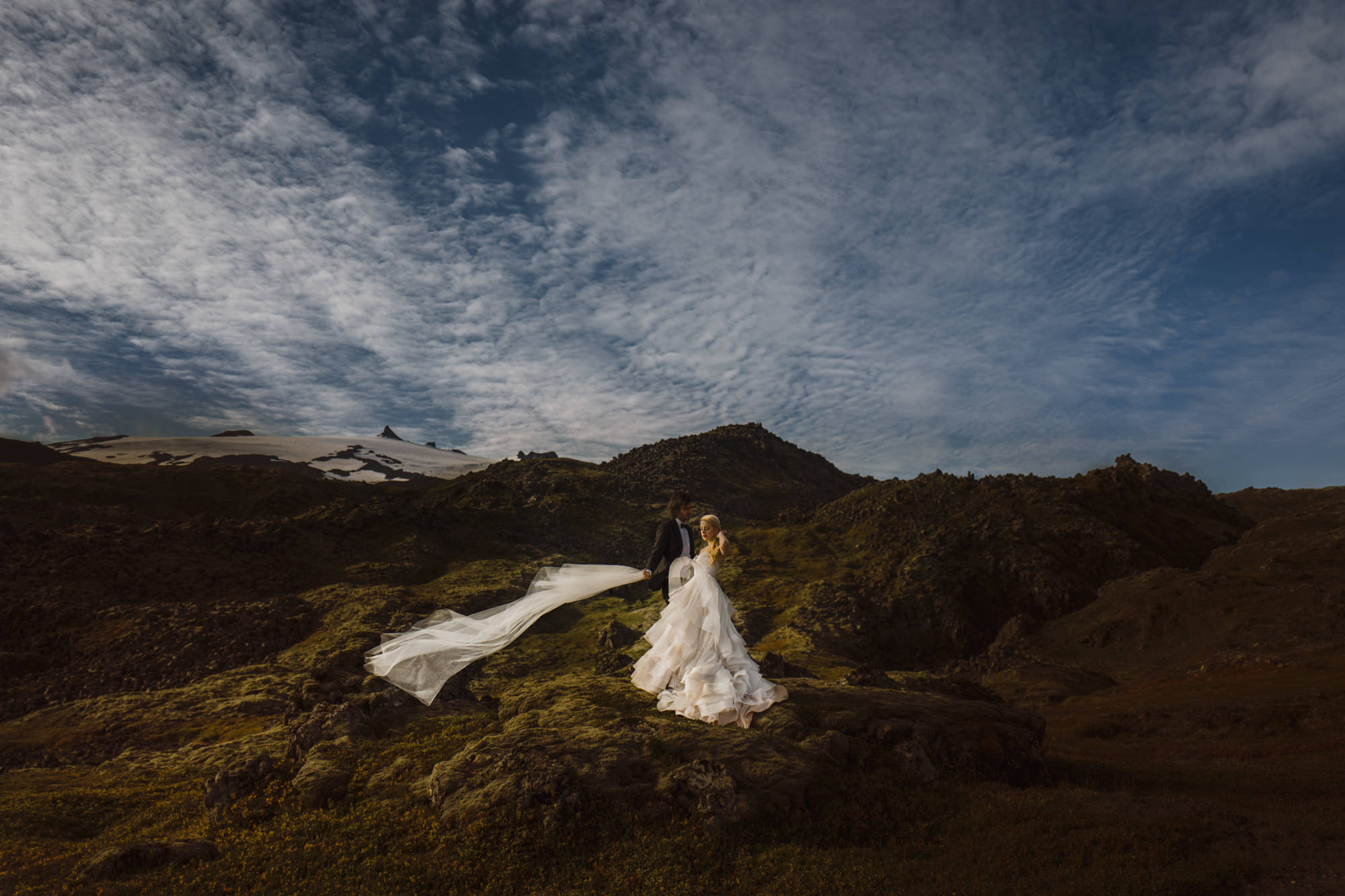 Groom holds veil for bride in mountain landscape - photo by McClintock Photography Agency