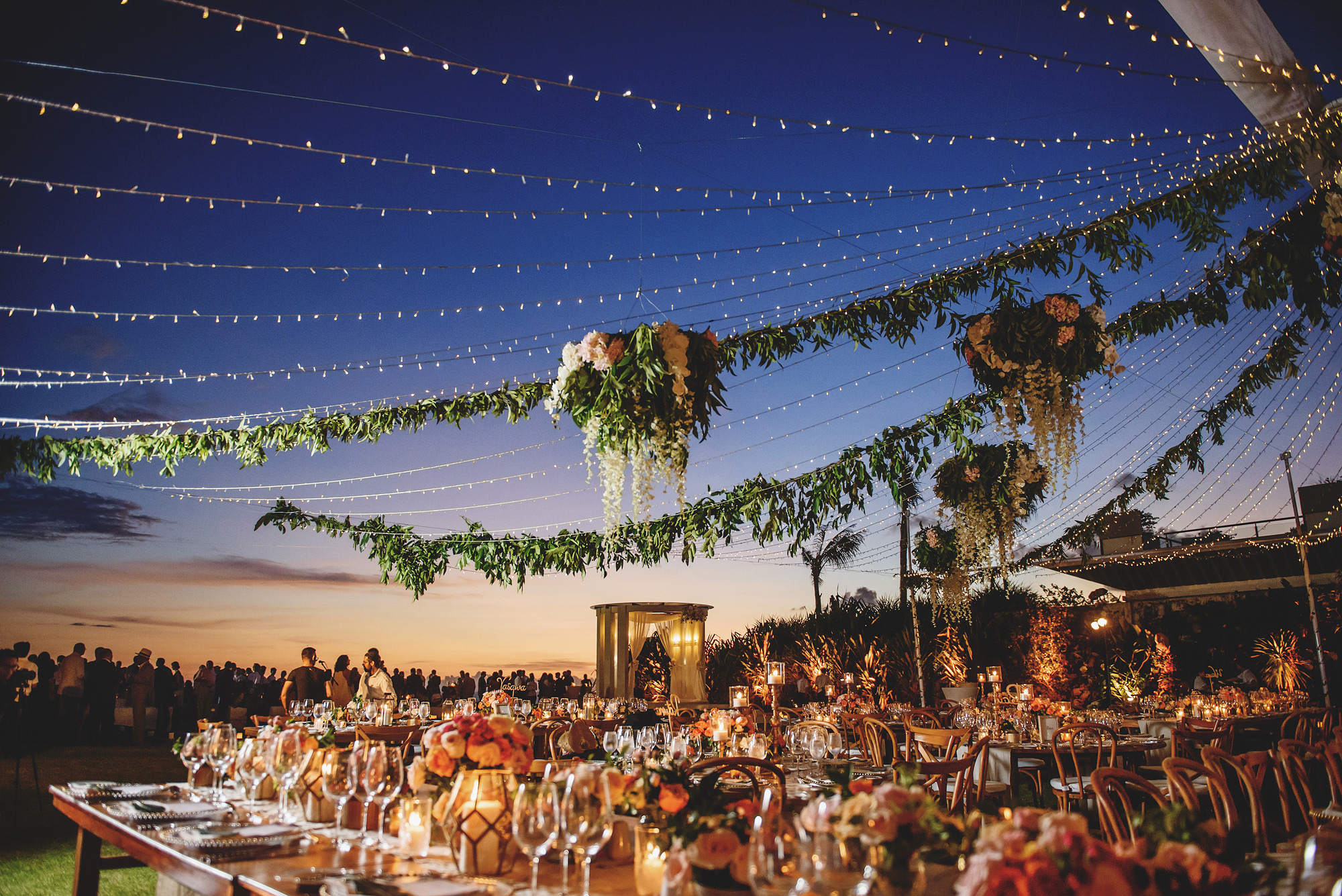 Luxury Wedding reception with floral wrapped lights - photo by Ross Harvey