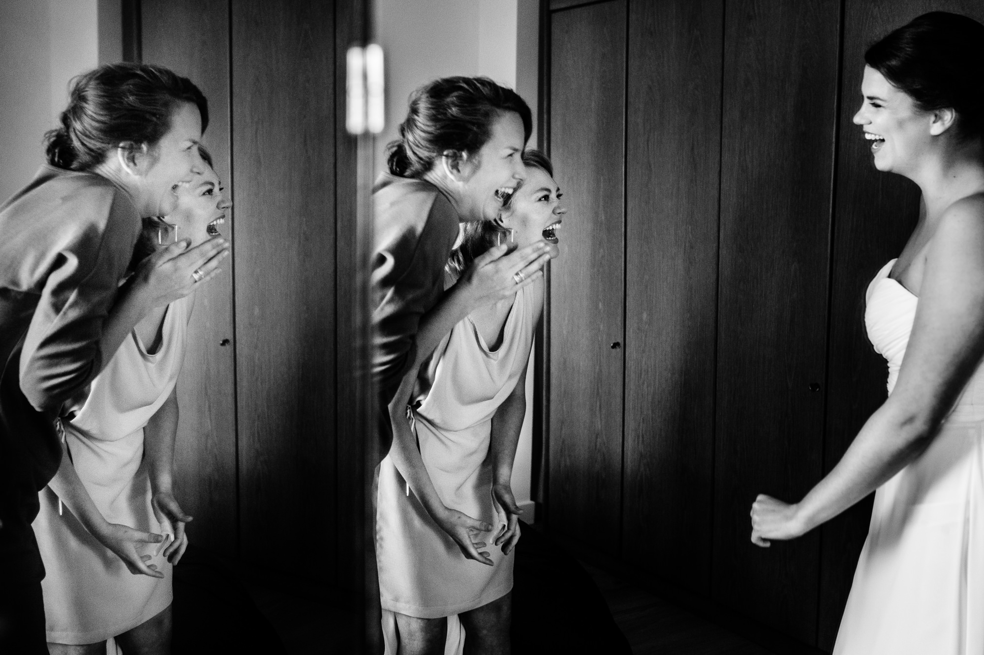 Laughing bridemaids reflected in mirror with bride Yves Schepers Belgium wedding photographers