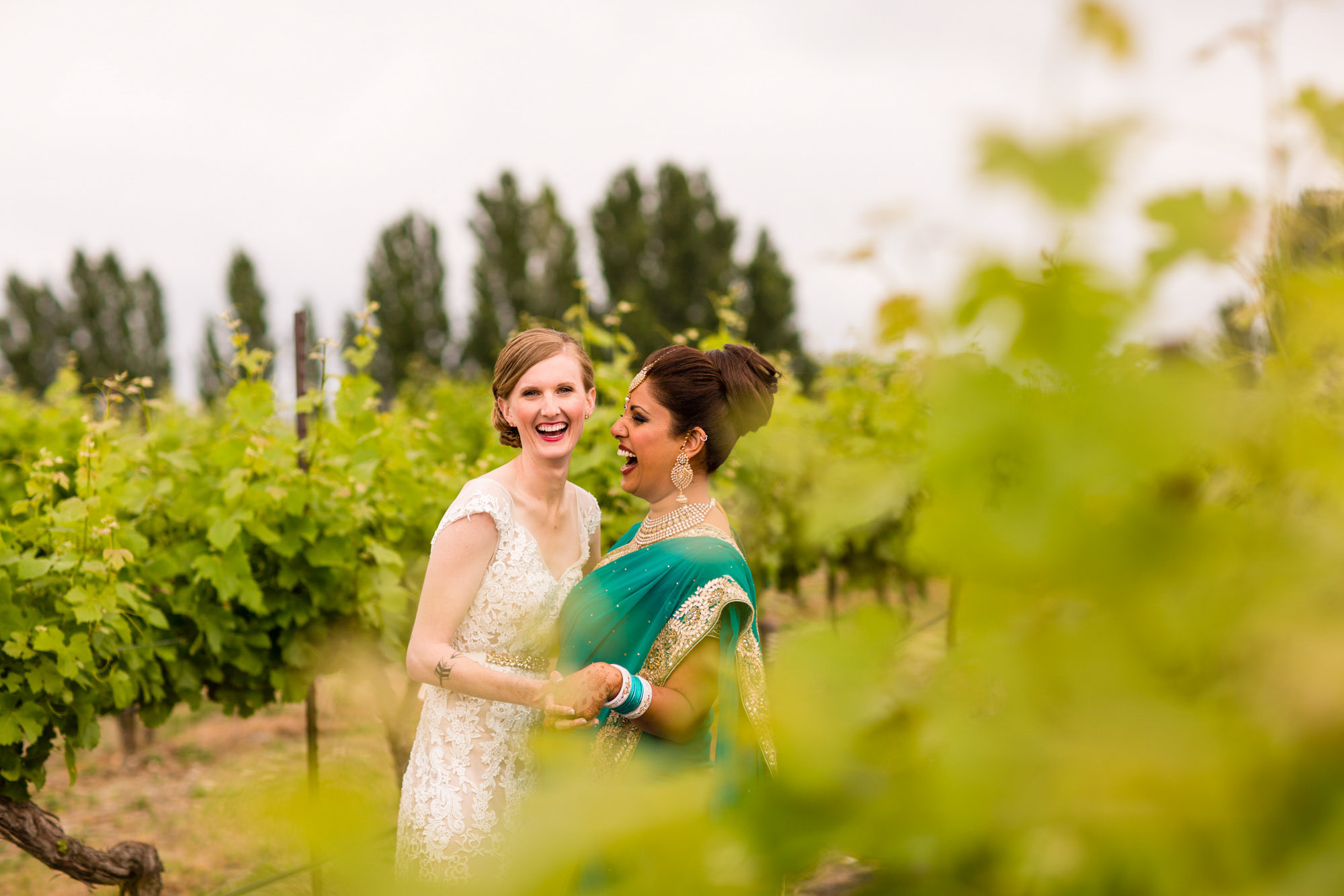 Two brides laughing in vineyard  - La Vie Photograph