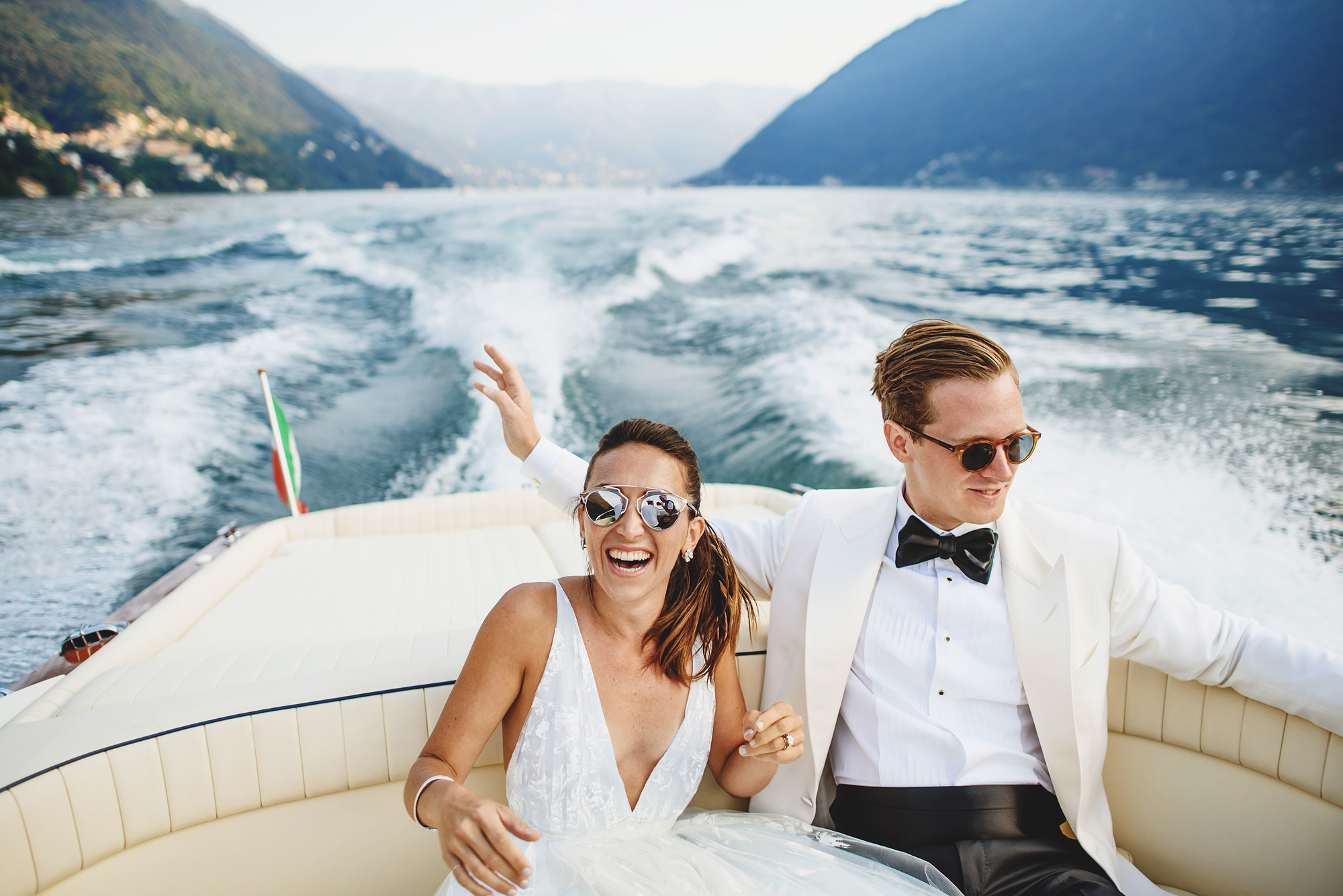 Laughing couple yachting on Lake Como - photo by Ross Harvey
