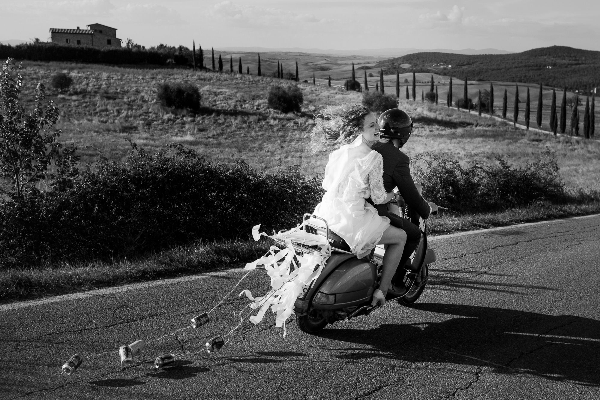 Laughing married couple leave ceremony on motorbike photo by Nordica Photography