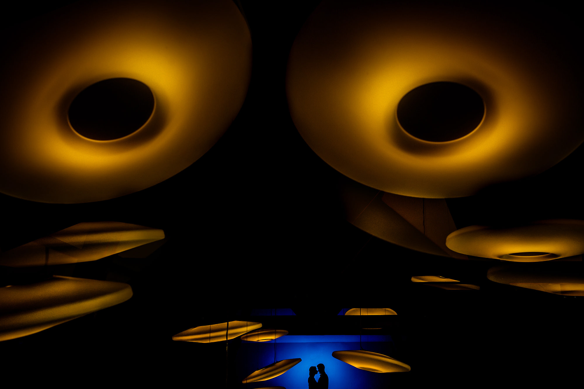 Silhouette of couple in blue light under golden sculptures by Eppel Photography