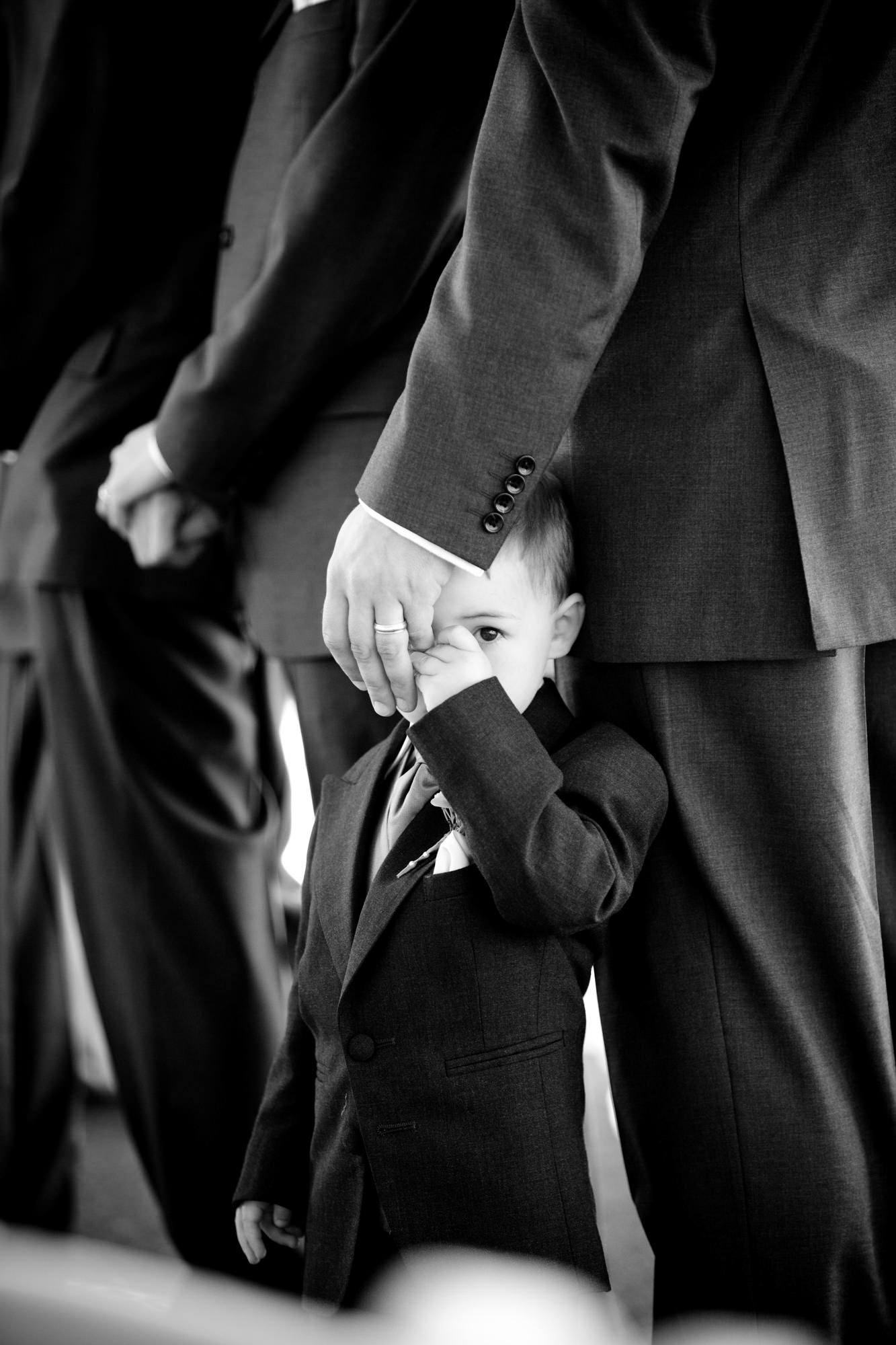 Little boy lookng shyly out from groomsmen's hand  -  La Vie Photography - San Juan Islands