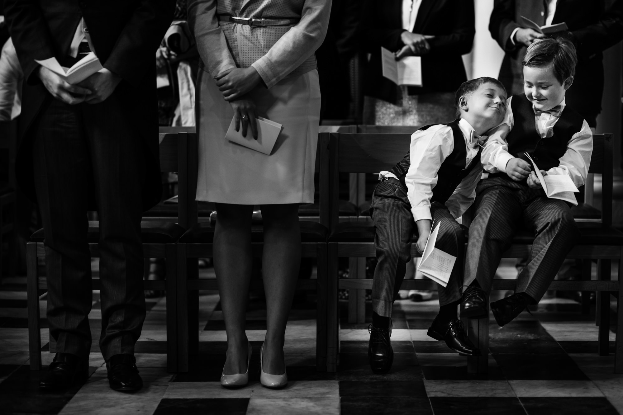 little  boy snuggles with brother on church pew  Yves Schepers Belgium wedding photographers