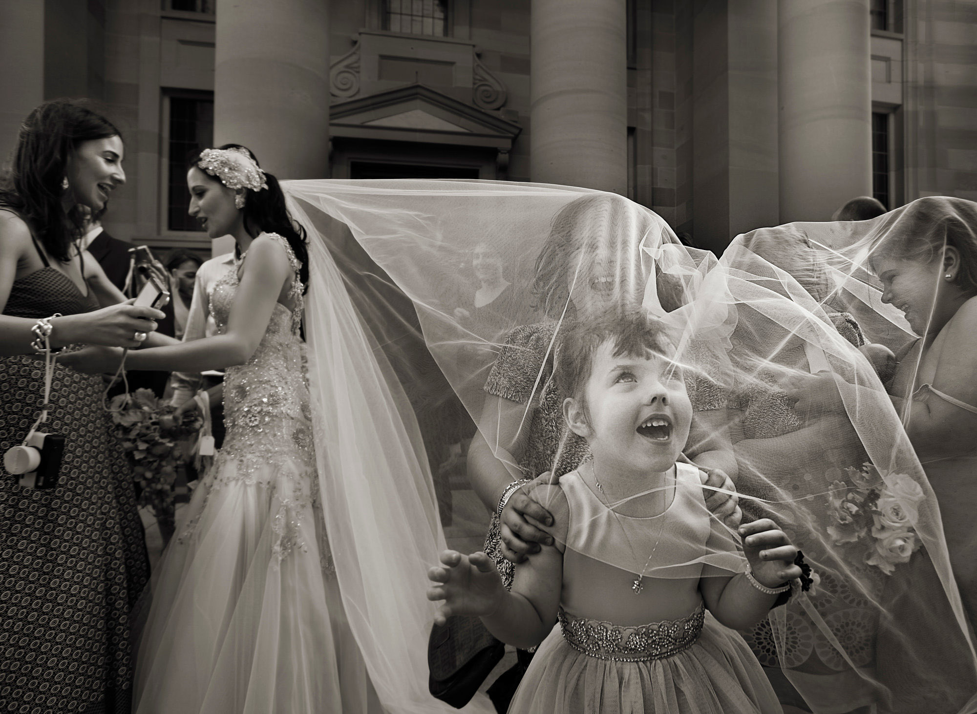 Little girl pokes nose into veil by Jerry Ghionis
