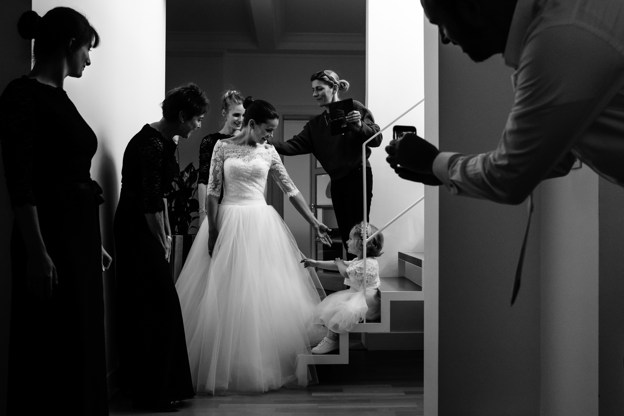 little girl reaches out to touch bride's dress Yves Schepers Belgium wedding photographers