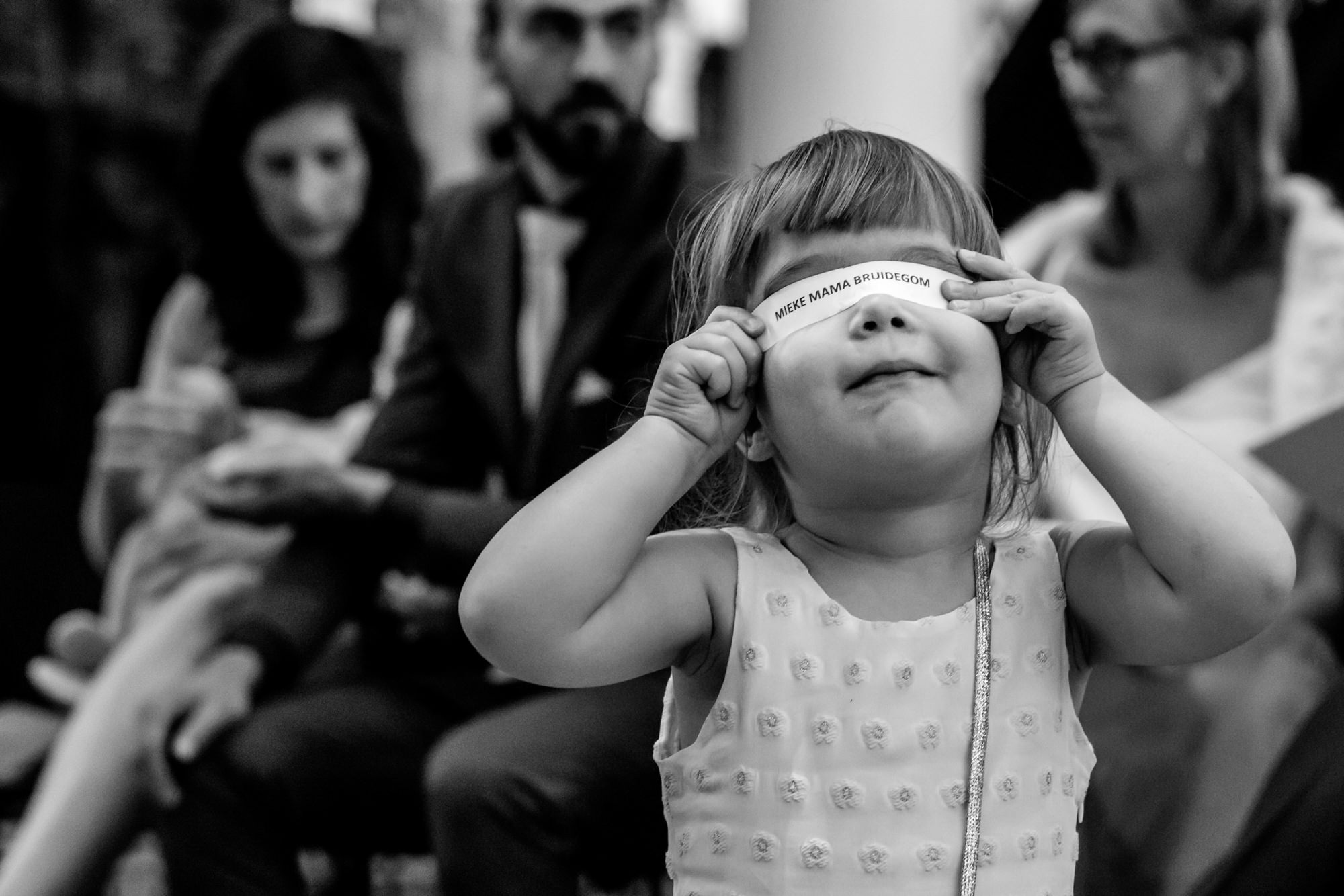 cute little girl hides her eyes with ribbon  - photo by Phillipe Swiggers