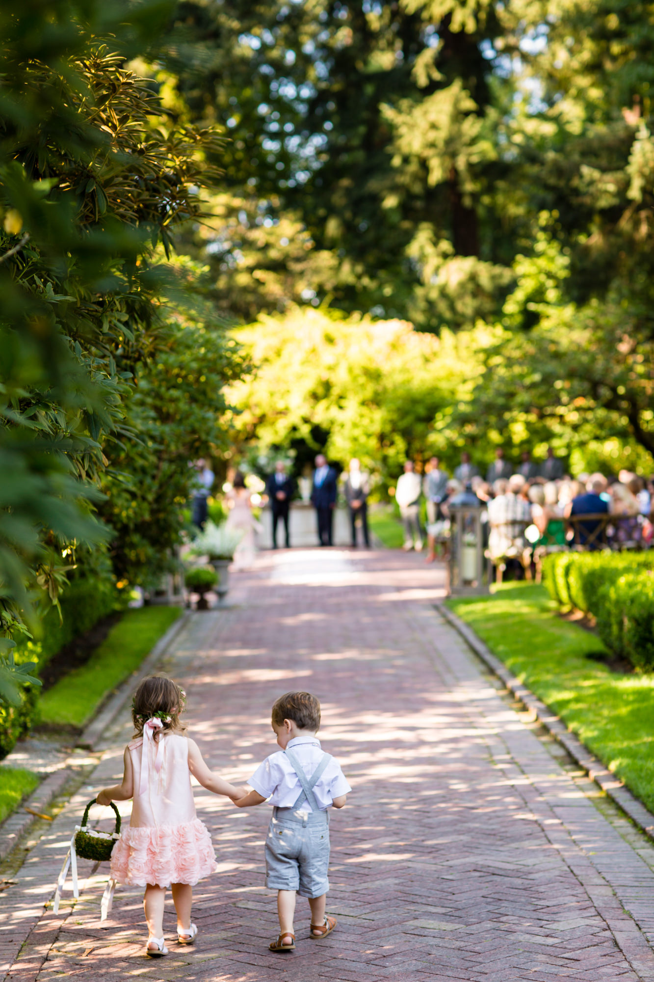 Ring bearer and flower girl hold hands down garden aisle - La Vie Photography