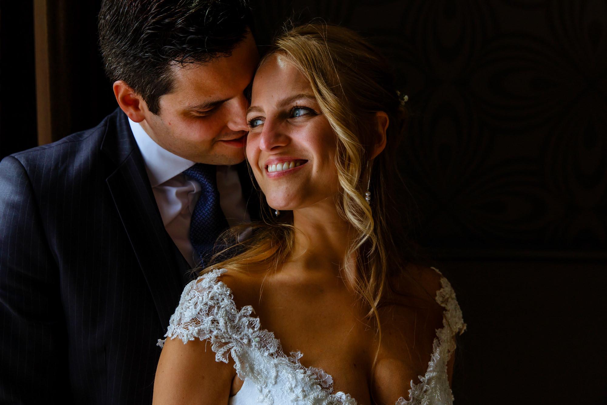 Portrait of bride and groom in windowlight by Phillipe Swiggers