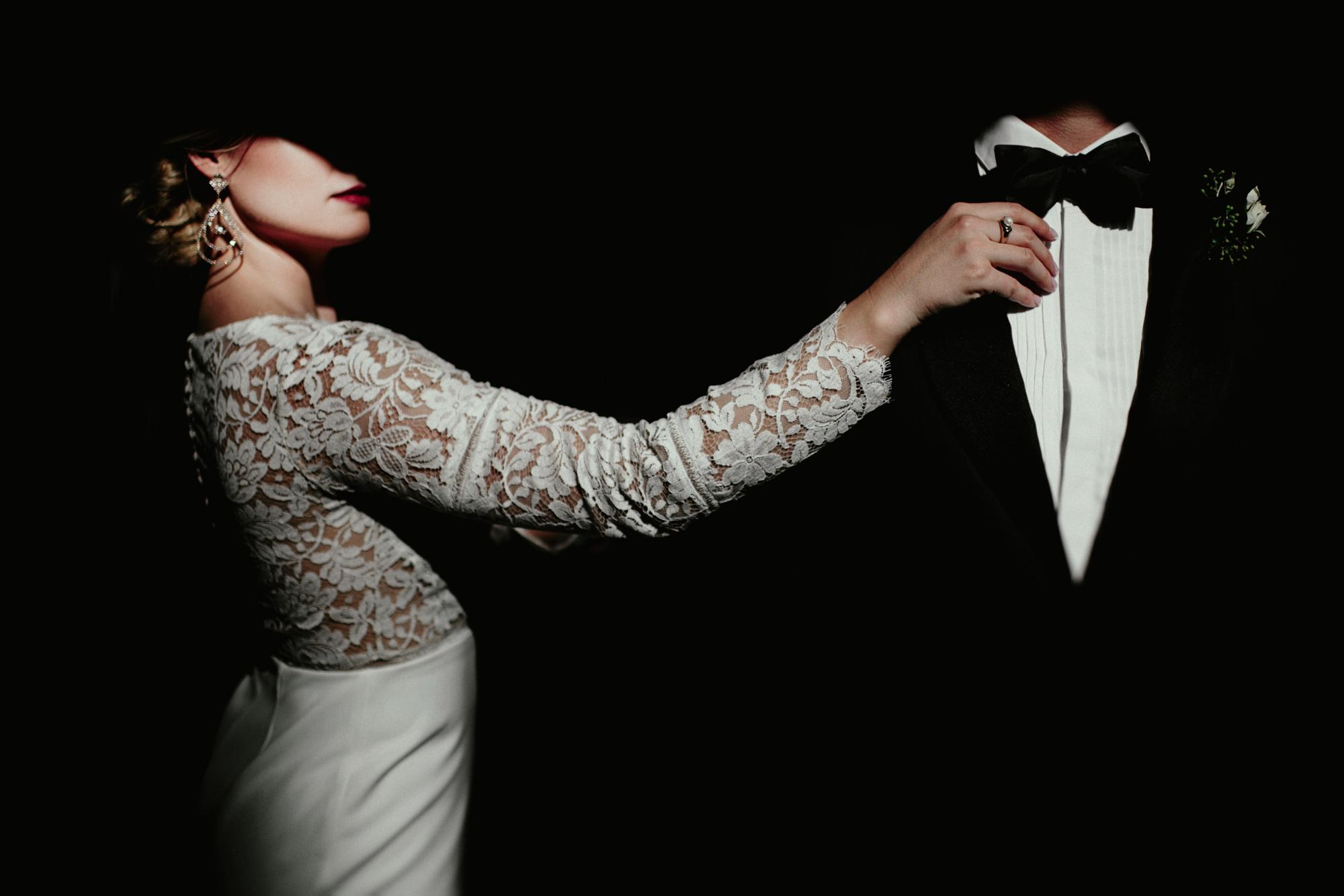 Photo of bride in long sleeve gown adjusting grooms tie by Fer Juaristi