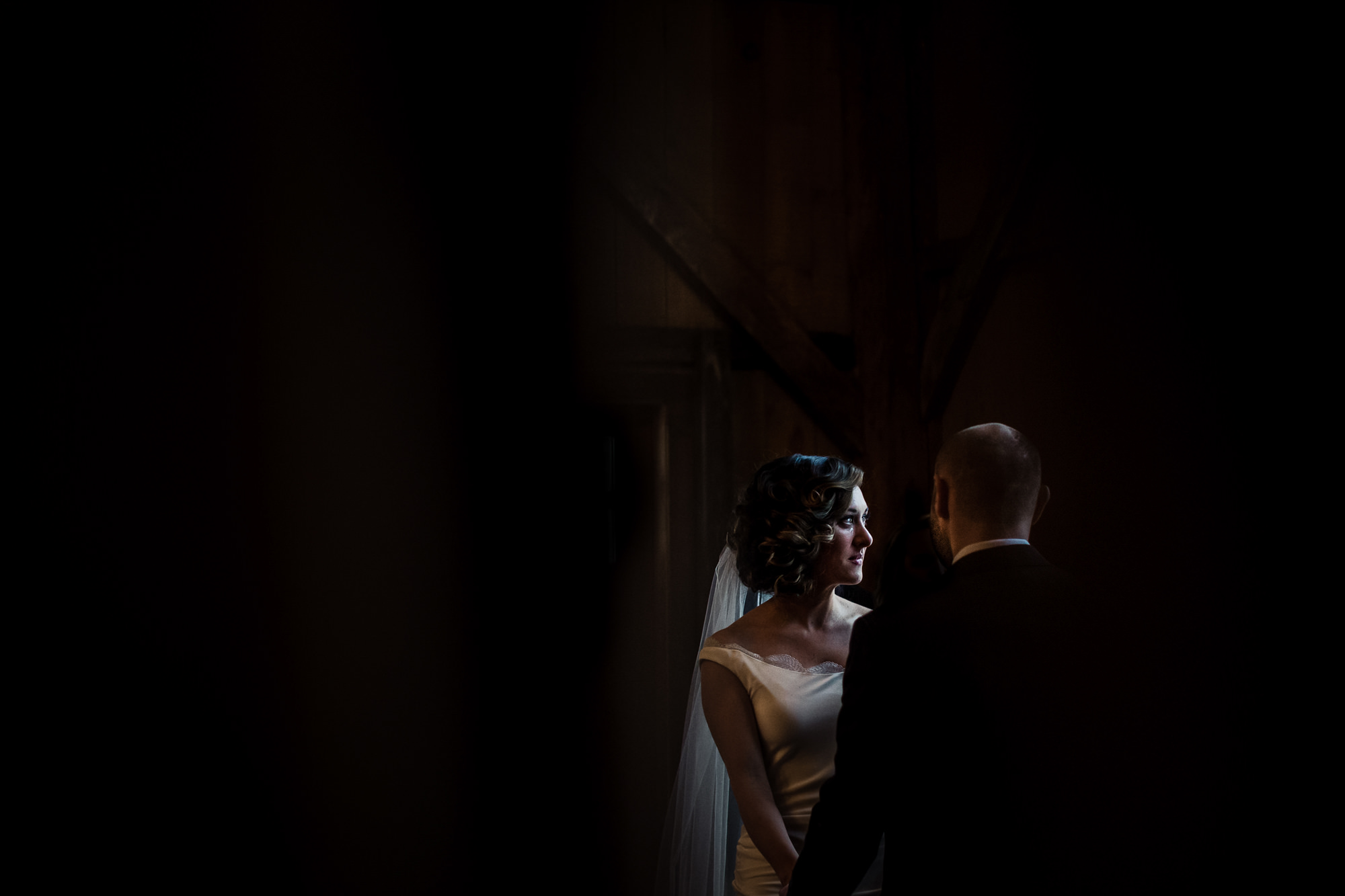 Tearful bride in silk gown and veil - photo by Jag Studios