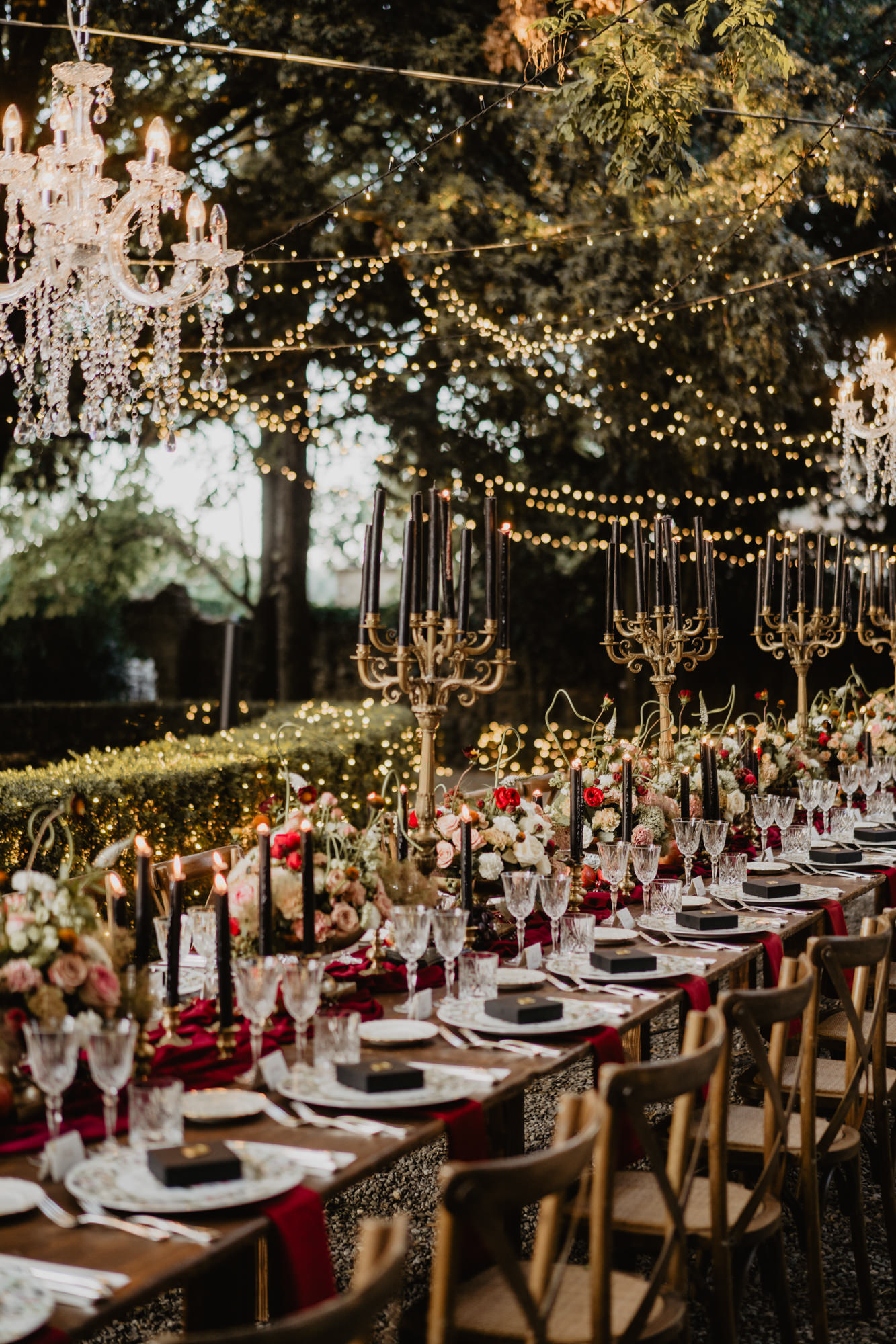 Luxury reception table with wood chairs and ivory cloth red rose runner, photo by David Bastianoni, Italy wedding photographer
