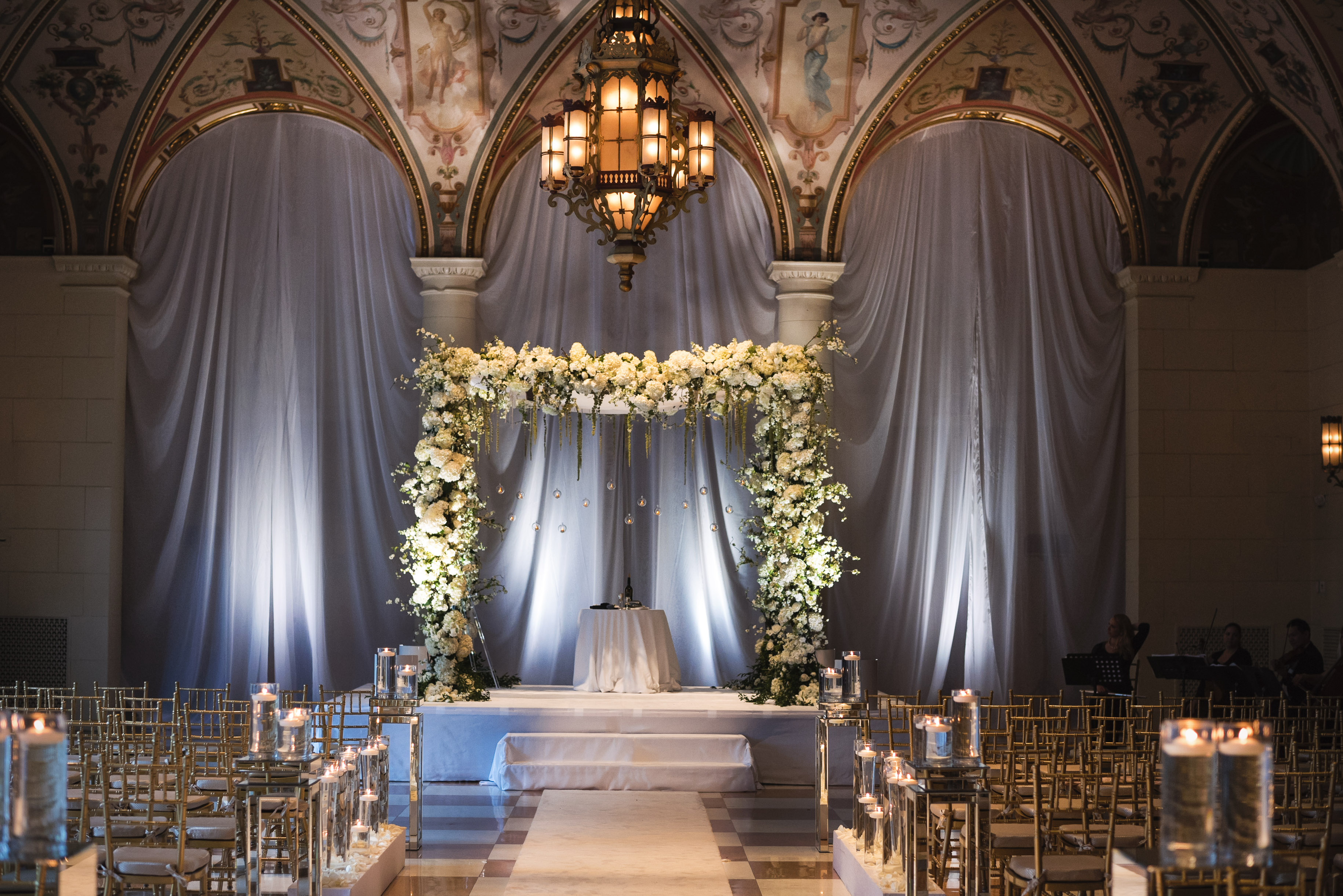 Luxurious white rose chuppah in grand ceremony ballroom, by Callaway Gable