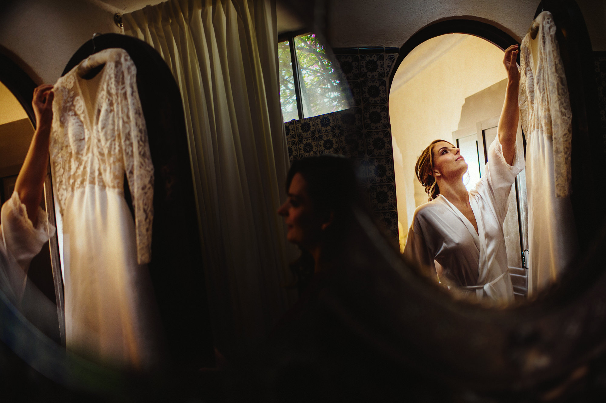 Bride in silk robe reaches for wedding gown - photo by Fer Juaristi