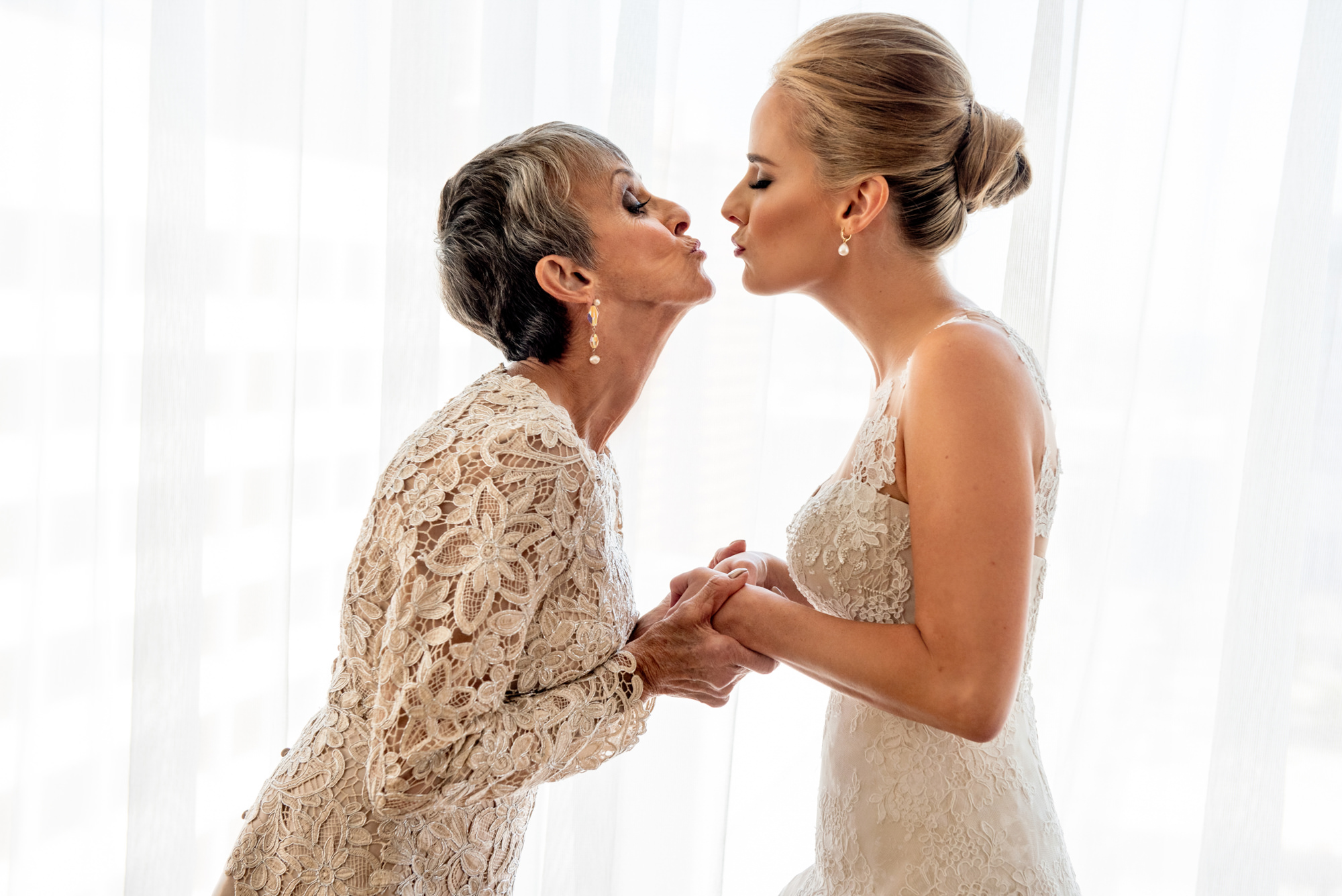 Mom kisses bride in ivory brocade gowns - Morgan Lynn Photography