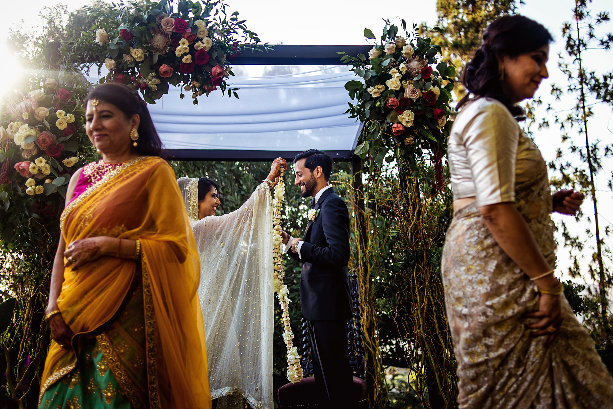 Mom of groom blesses with floral garland -  photo by Davina + Daniel