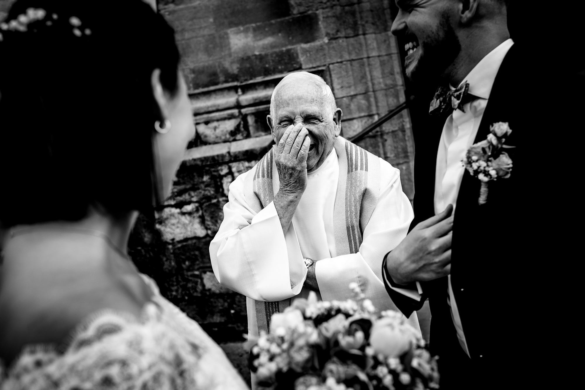 Sweet photo of priest laughing by Eppel Photography
