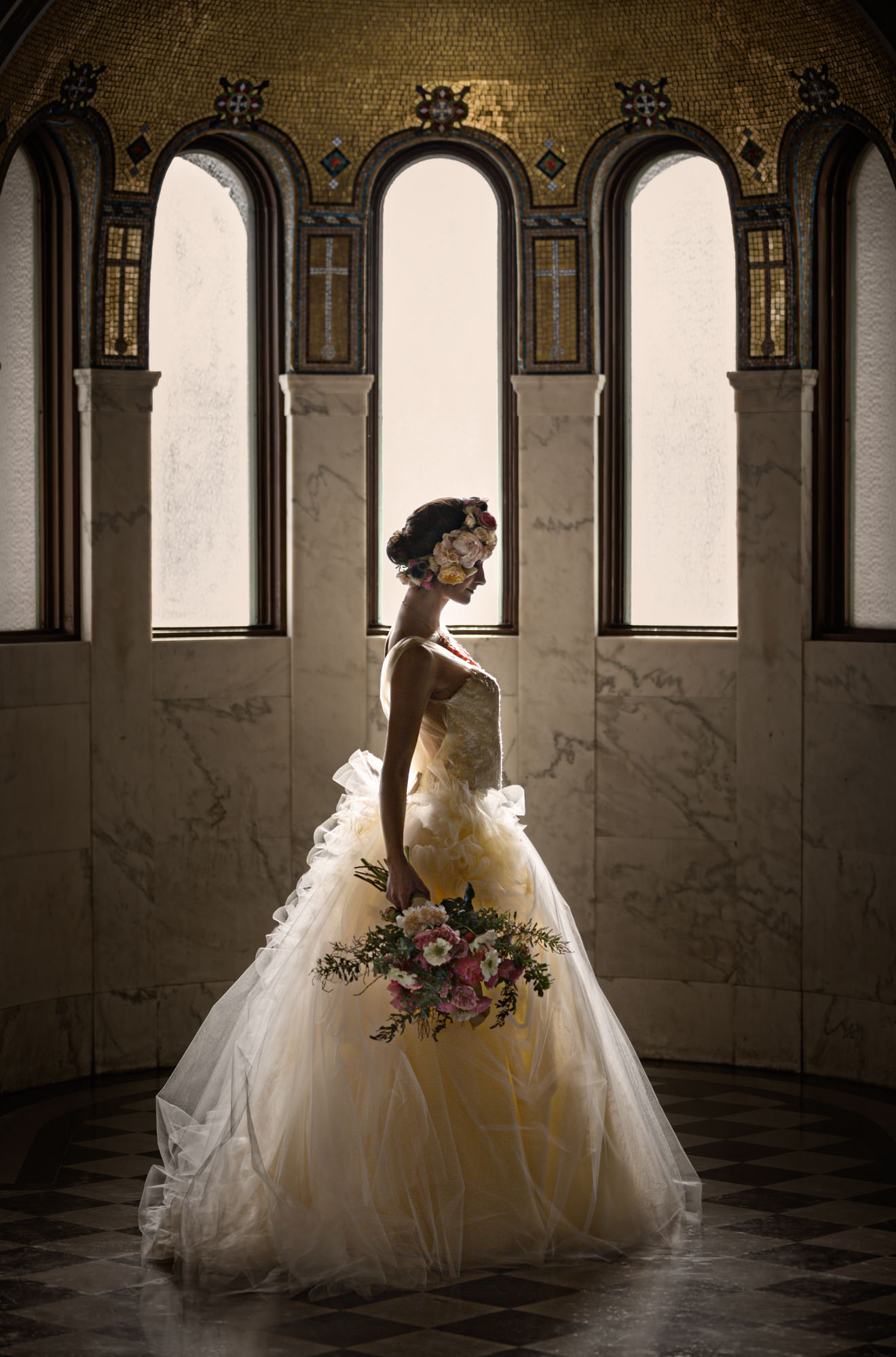 Profile of bride in Monique Lhuillier ballgown with bouquet and floral crown by Roberto Valenzuela