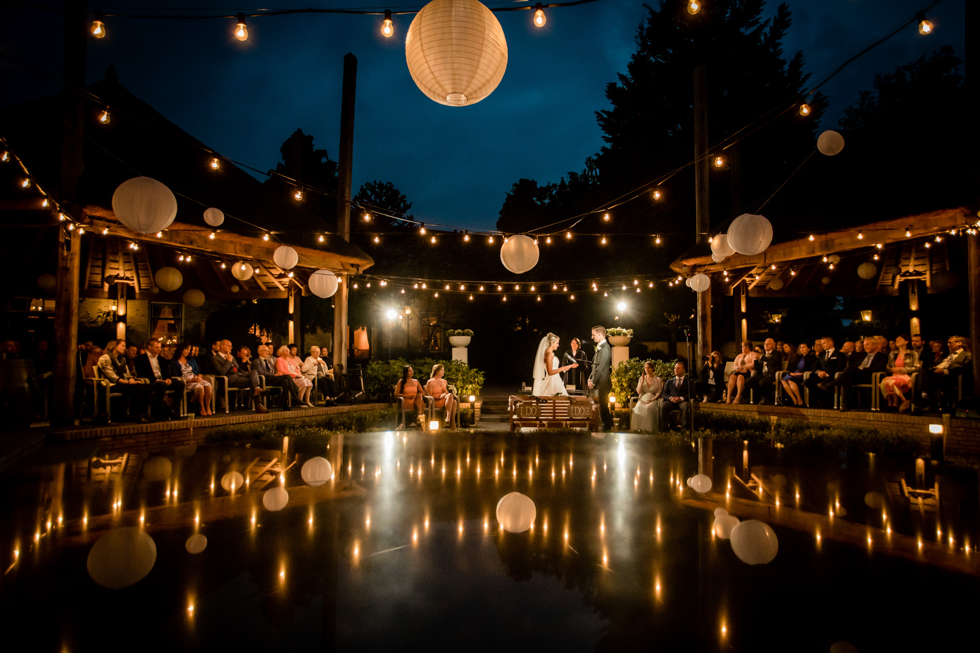 Outdoor evening ceremony with paper lanterns by Eppel Photography