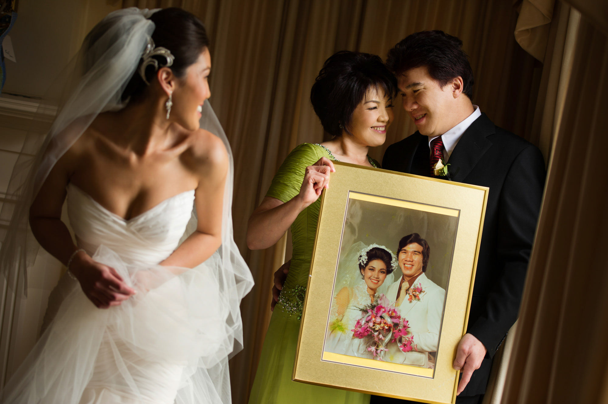 Parents holding photo of their wedding with bride by Jerry Ghionis luxury wedding photographer