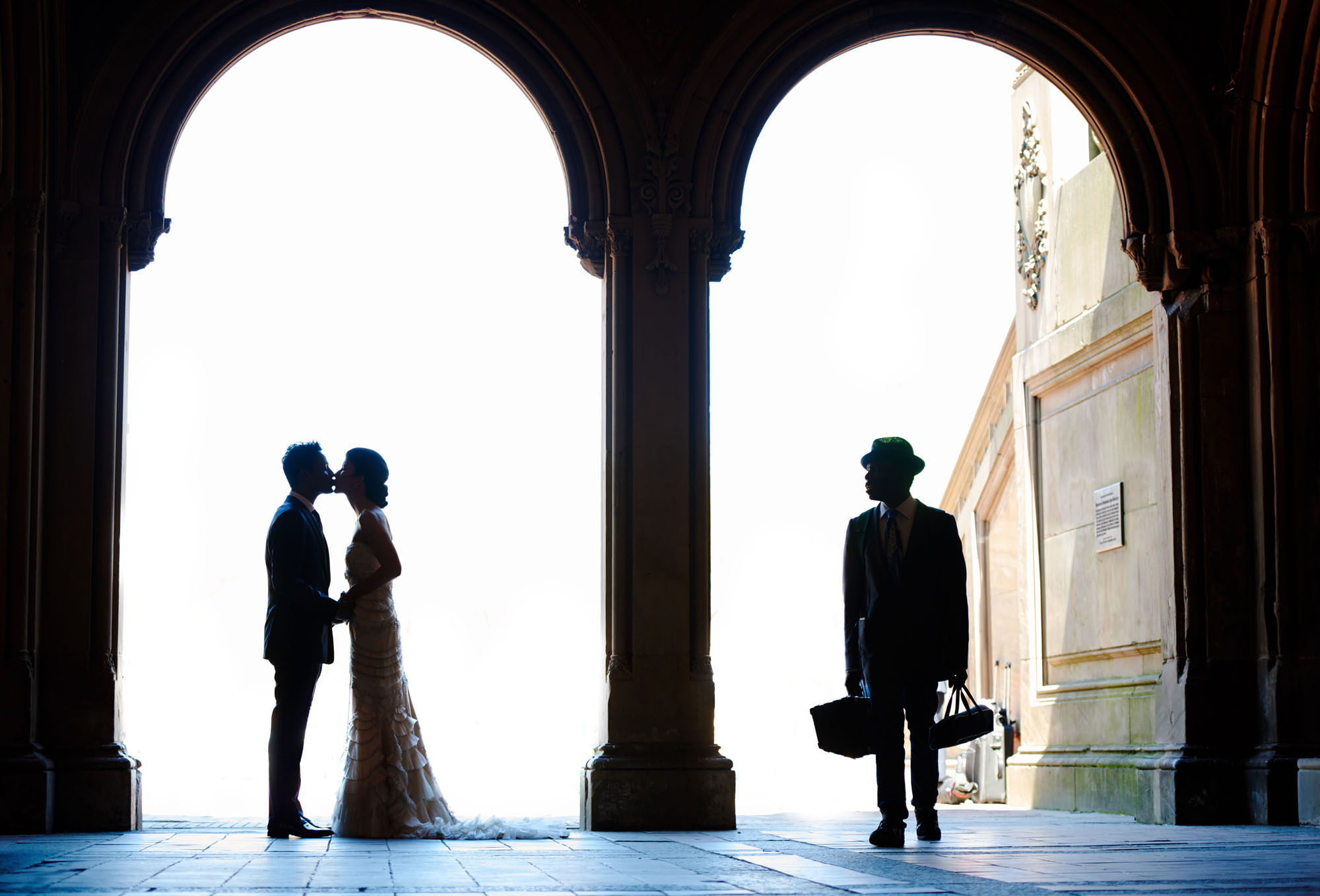 Silhouette of couple kissing under arch while stranger looks on - photo by The Brenizers