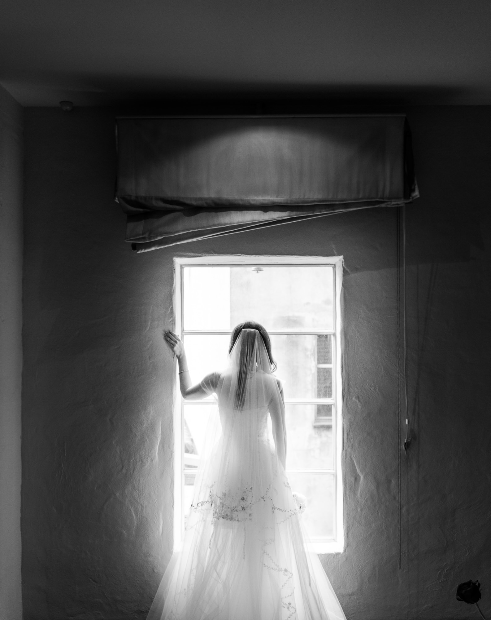 Pensive bride looking out window -  photo by Marcus Bell