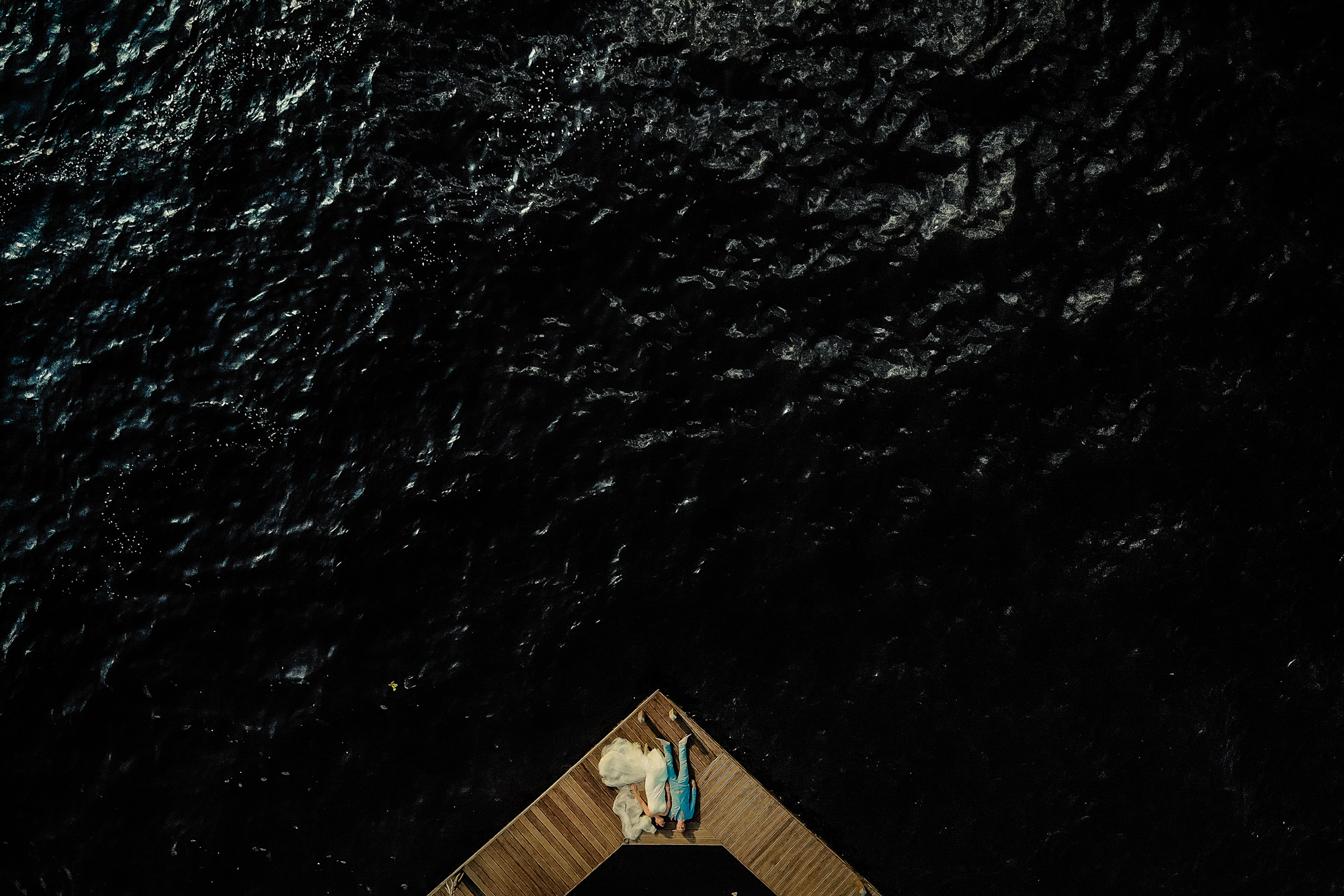 Creative composition of bride and groom on dock by Eppel photography