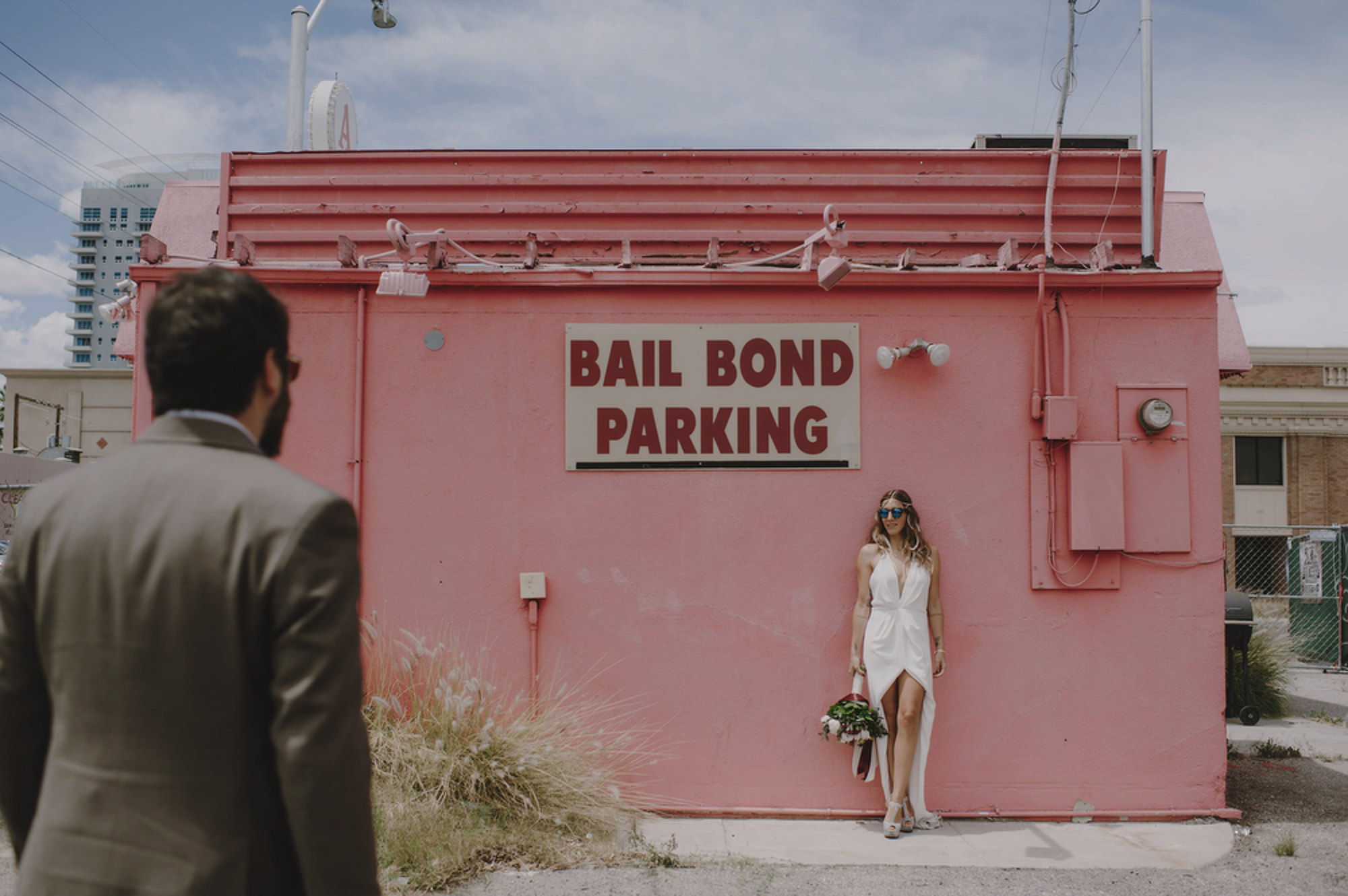Portrait with bride in sexy white dress in front of Bail Bond shop  - photo by Kristen Marie Parker
